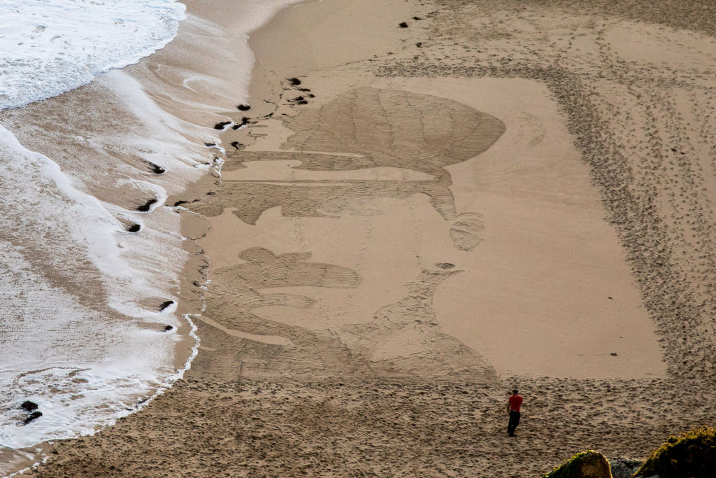 People on Porthcurno beach watch as waves wash away a large scale sand portrait of Lieutenant Richard Charles Graves-Sawle, one of a number from the project called Pages of the Sea near Penzance on November 11, 2018 in Cornwall, United Kingdom.