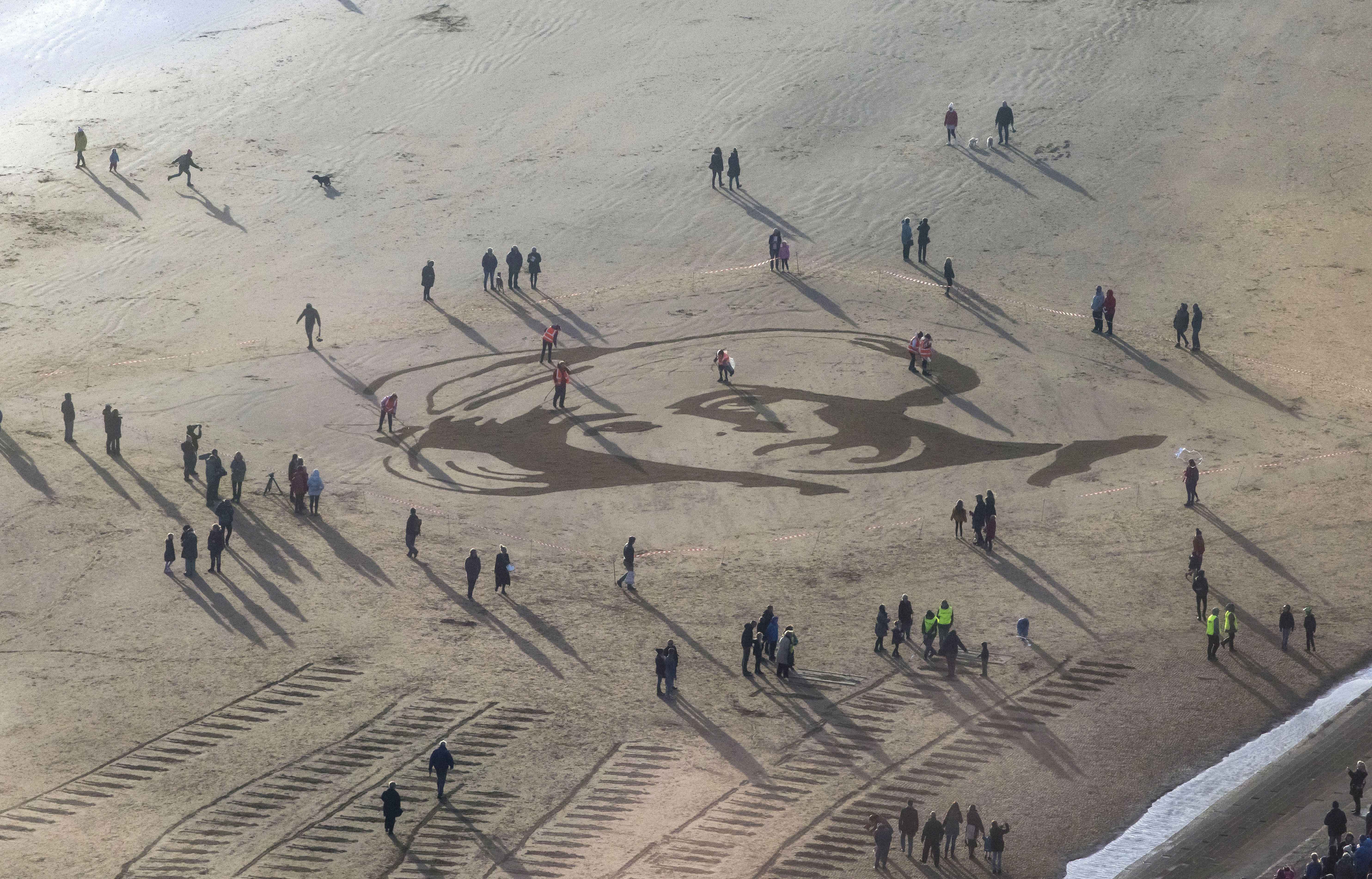 Members of the public gather on Swansea Bay Beach, Wales, for filmmaker Danny Boyle's Pages of the Sea, commissioned by 14-18 NOW to mark the centenary of Armistice Day on November 11, 2018 in Swansea, Wales.