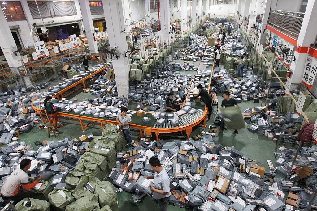 Express shipping crews deal with packages on an assembly line in Wenzhou, Zhejiang, China on Nov. 12, 2014.