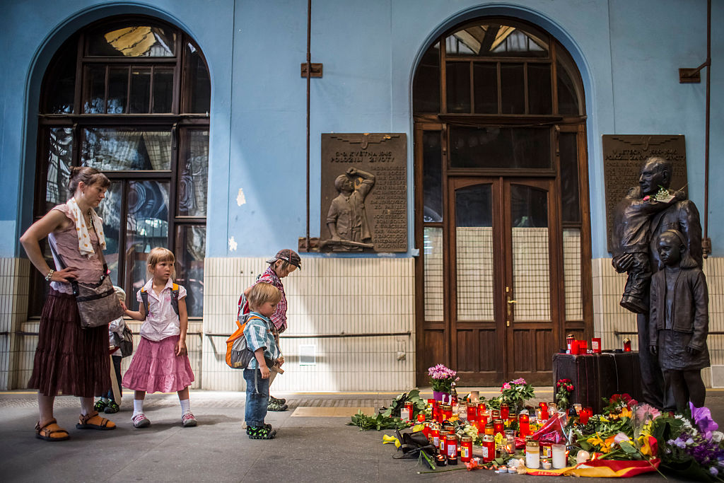A woman and children pay respect at the statue of Sir Nicholas Winton at the main train station in Prague, Czech Republic, on July 2, 2015.. Winton saved 669 mostly Jewish children from the Nazis by organising their escape from occupied Czechoslovakia to the U.K.