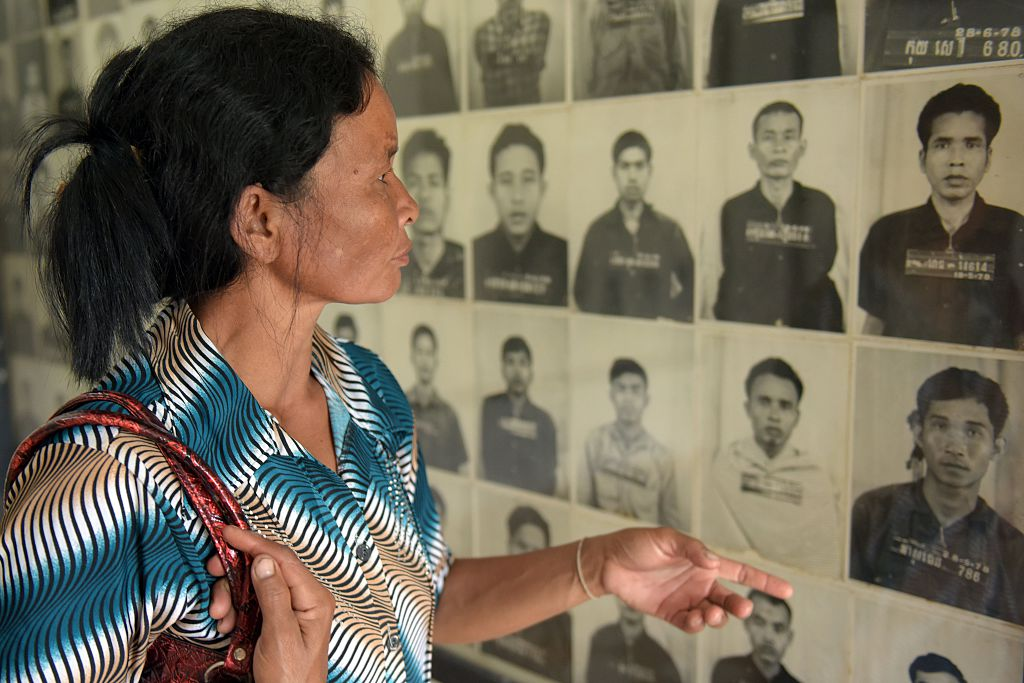 A Cambodian woman looks at portraits of victims of the Khmer Rouge at the Tuol Sleng genocide museum (S-21) in Phnom Penh, Cambodia on Aug. 24, 2015.