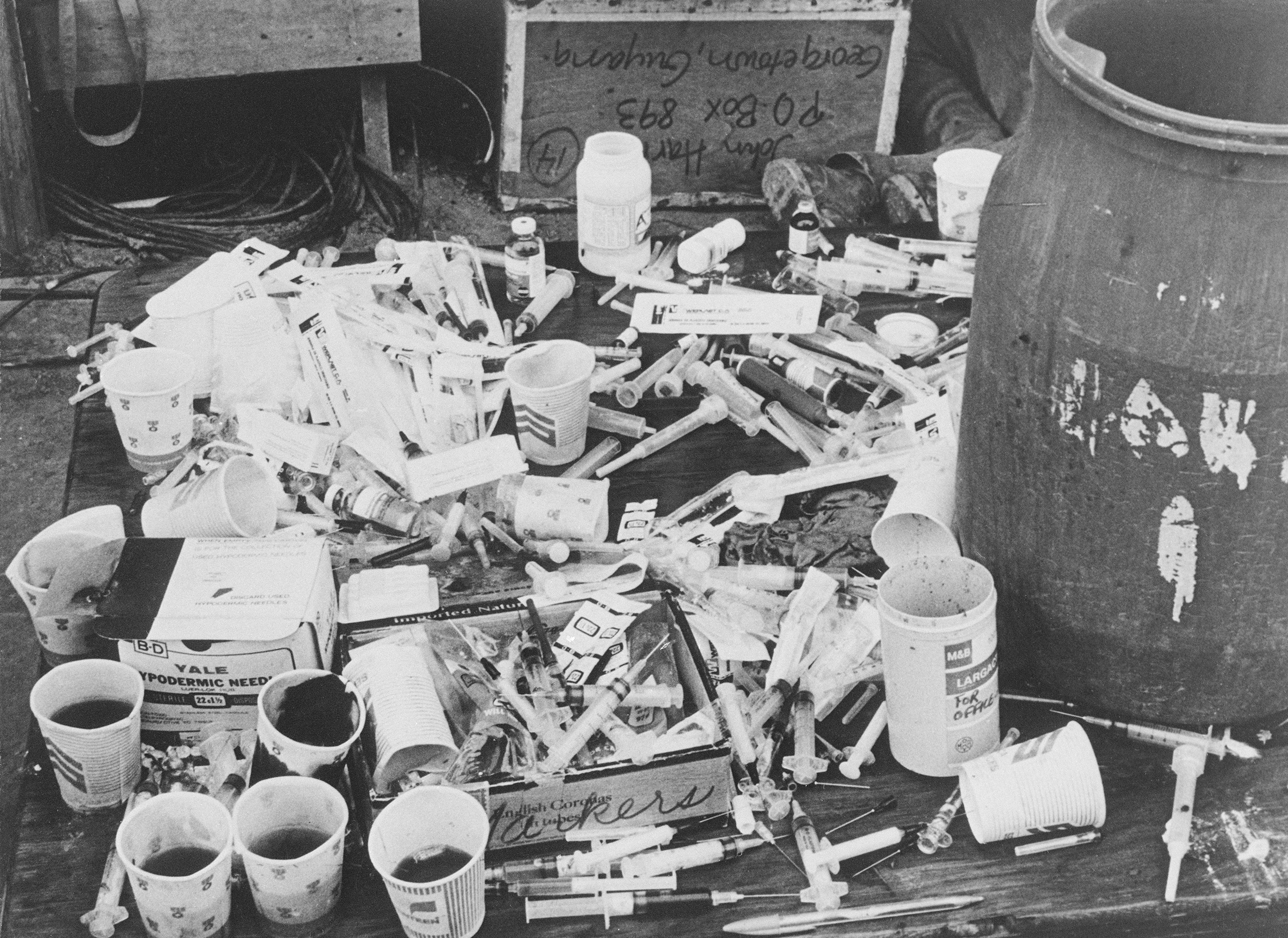 A pile of paper cups with cyanide-laced fruit punch, and a pile of hypodermic syringes, found at Jonestown by Guyanese officials.