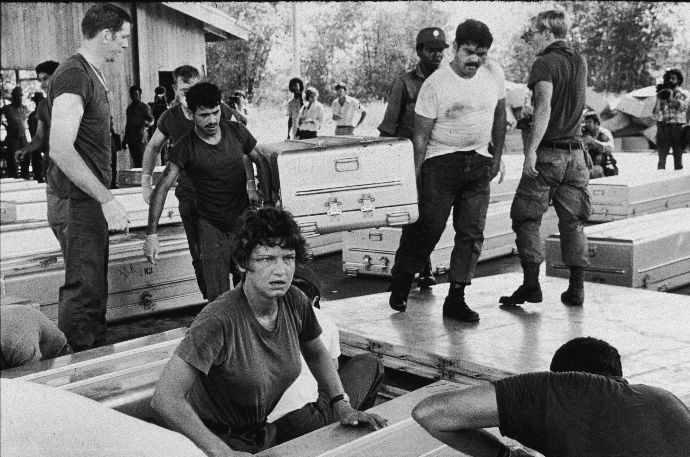 Members of a U.S. military team prepare aluminum coffins for shipment to the United States, following the more than 900 deaths in the mass suicide staged in Jonestown by members of the People's Temple and their leader, the Reverend Jim Jones, Georgetown, Guyana, Nov. 24, 1978.