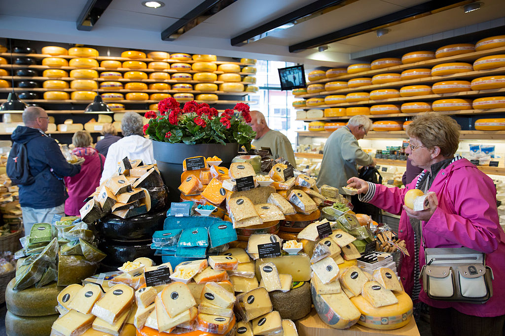 Tourists shopping at a traditional cheese shop in Gouda, The Netherlands.