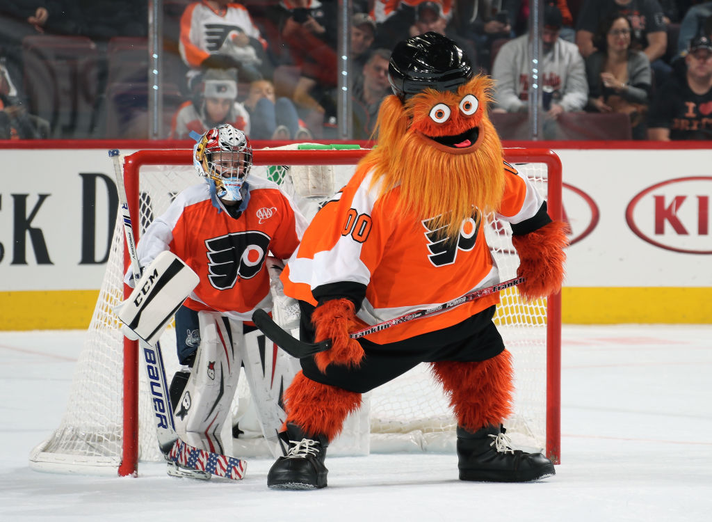 PHILADELPHIA, PA - OCTOBER 09:  Gritty the mascot of the Philadelphia Flyers plays hockey with a member of the mites on ice during the second intermission against the San Jose Sharks on October 9, 2018 at the Wells Fargo Center in Philadelphia, Pennsylvania.  (Photo by Len Redkoles/NHLI via Getty Images)