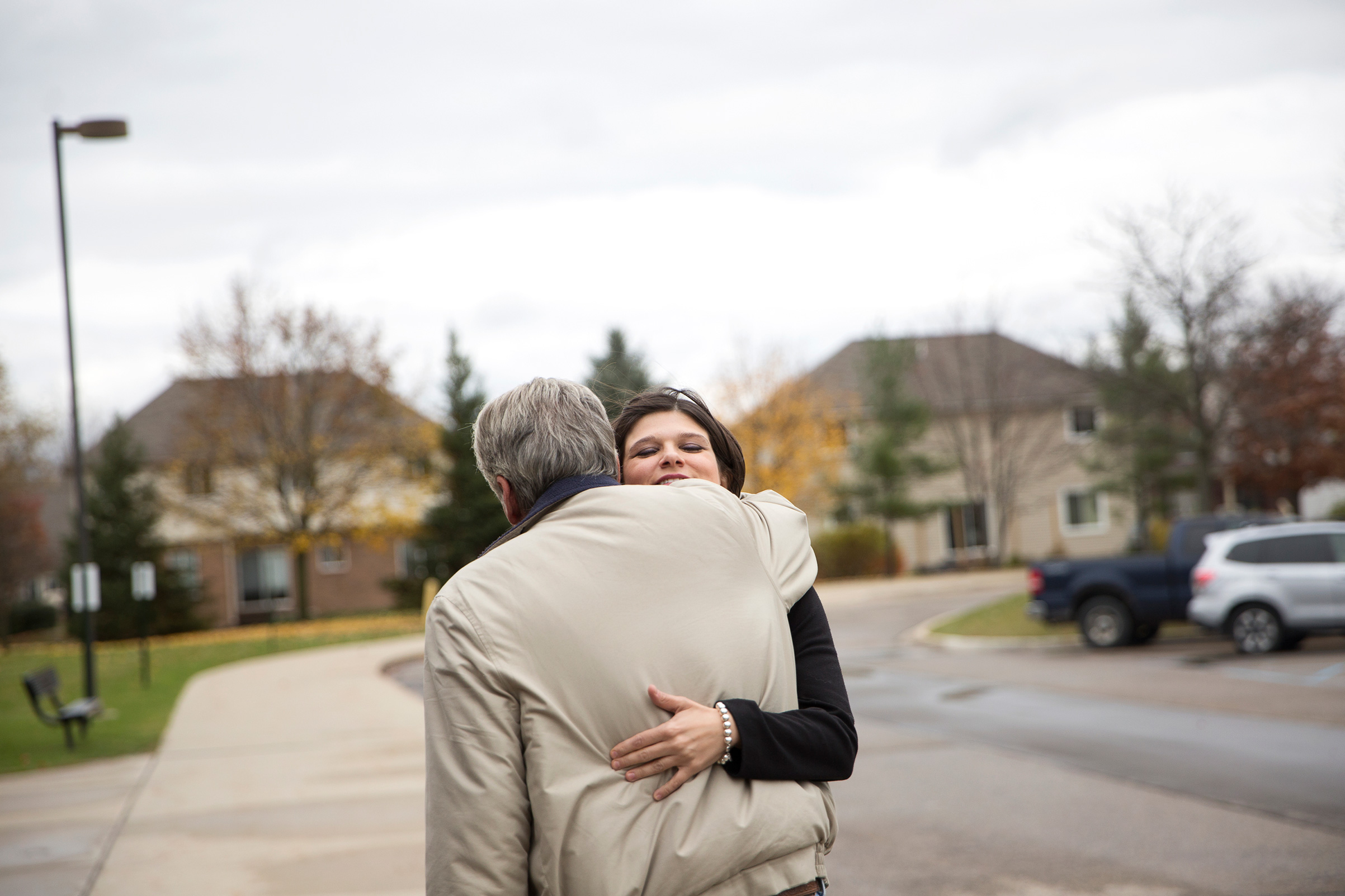 Democratic candidate for Michigan's 11th Congressional District Haley Stevens hugs her neighbor after running into him while voting at Deerfield Elementary School in Rochester Hills, Mich, on Tuesday, Nov. 6, 2018.