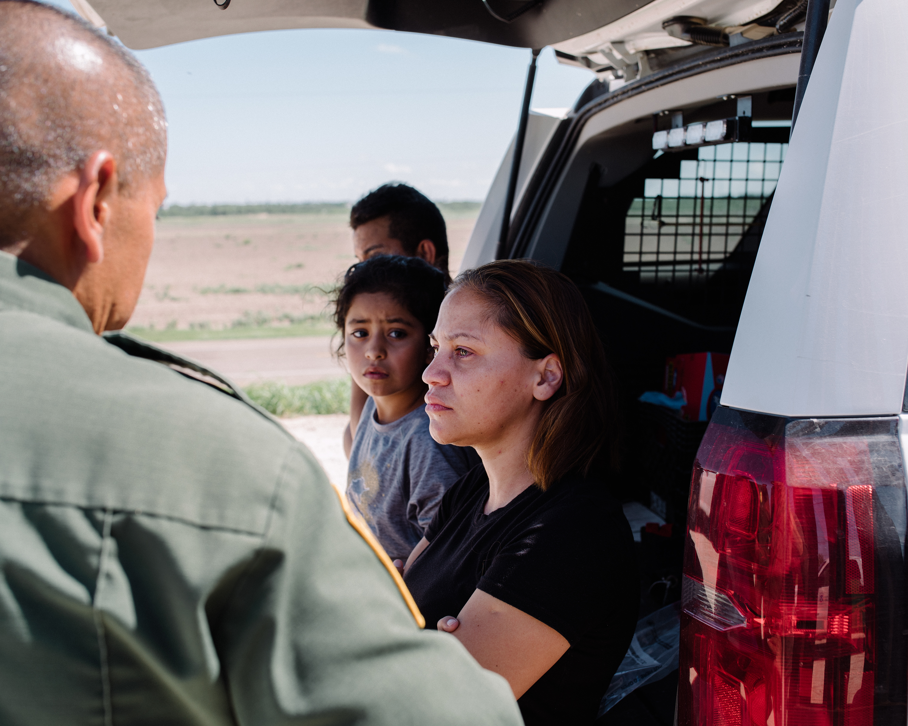 Miriam Castillo Castillo, next to her young niece, speaks with a border officer after crossing the river to McAllen on Sept. 25; members of their group said they were fleeing politically motivated violence at home.