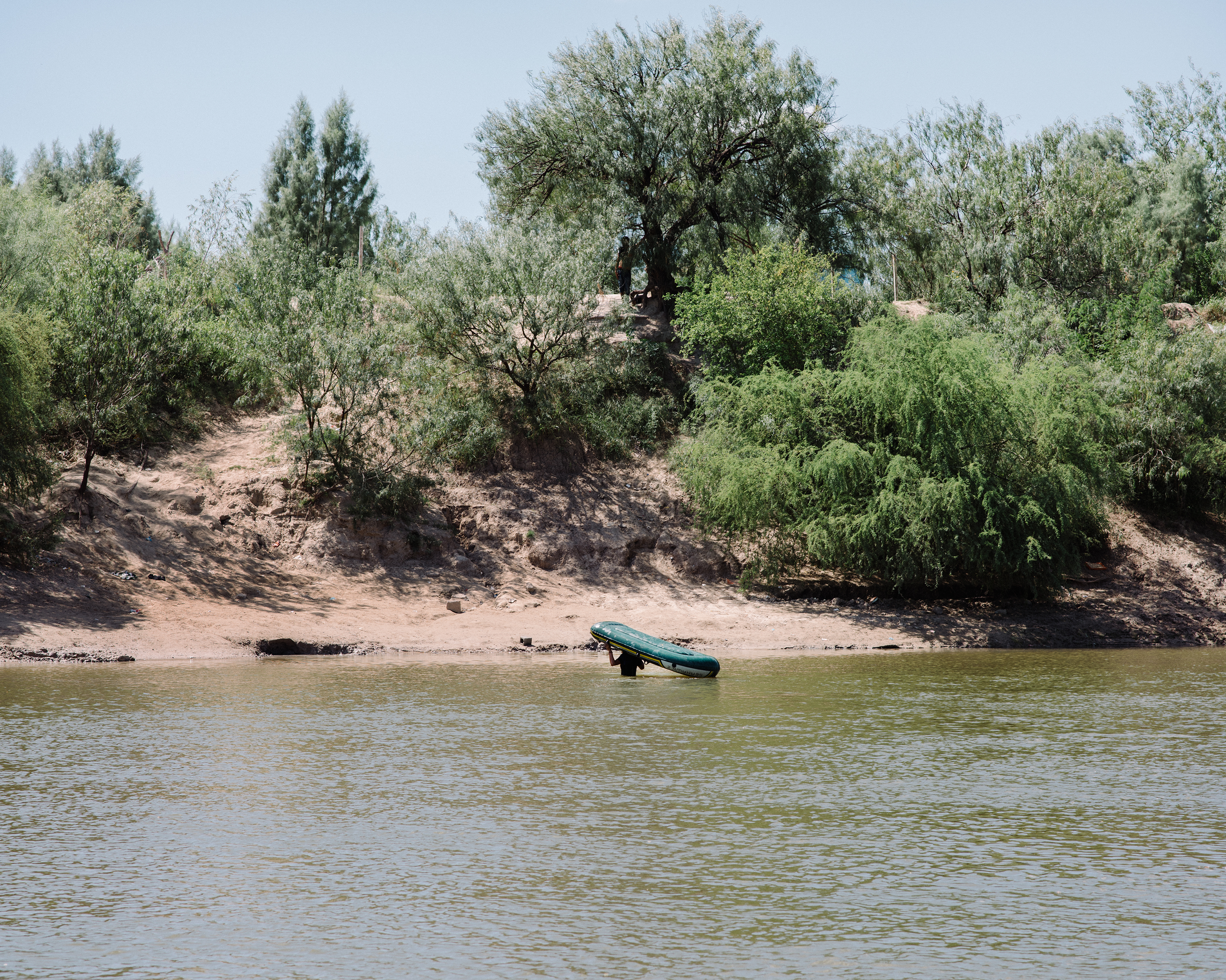 A trafficker returns to the Mexican side of the Rio Grande after paddling over two Nicaraguans on Sept. 25.