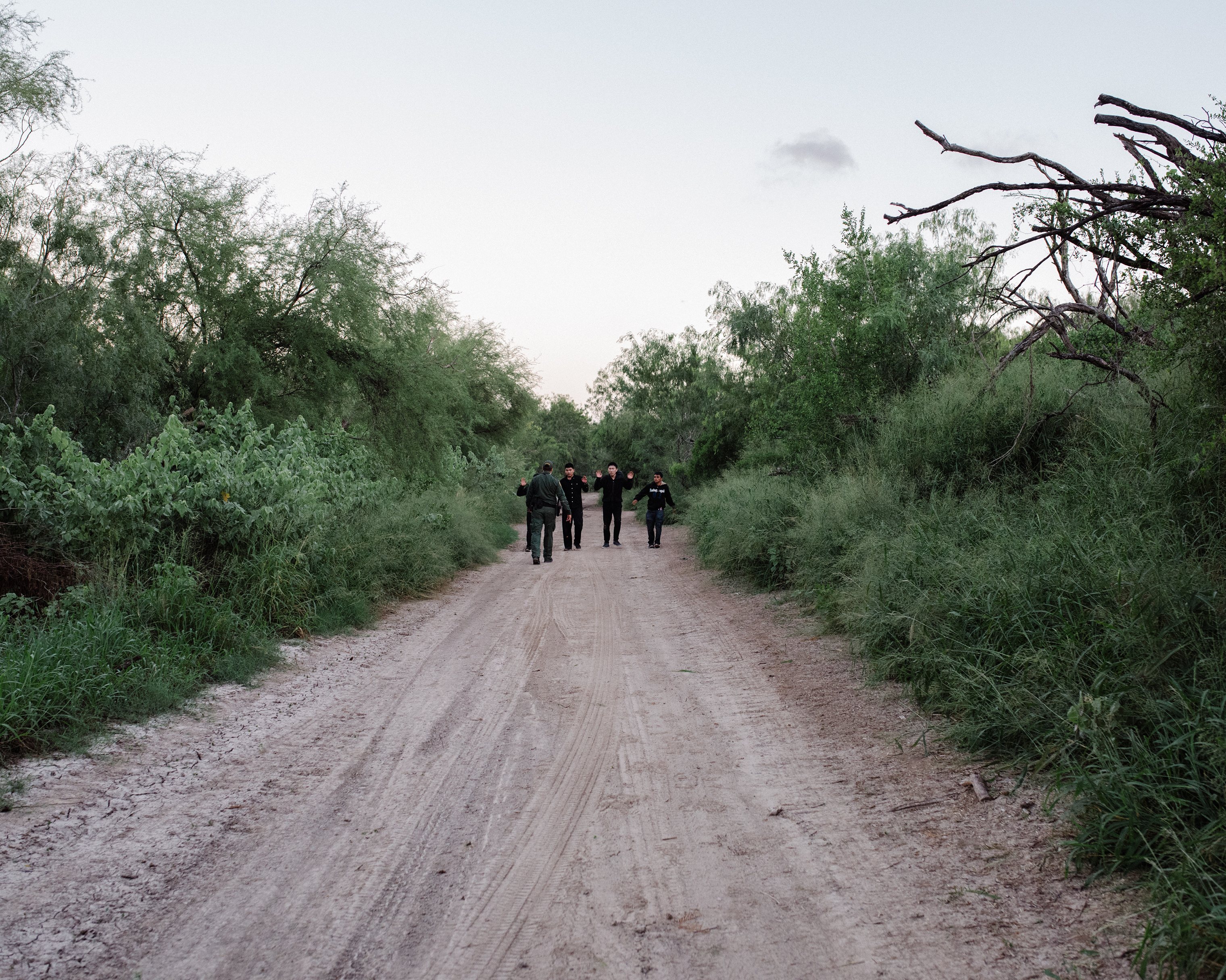 Migrants who crossed the Rio Grande into McAllen are approached by a border officer on Sept. 25.