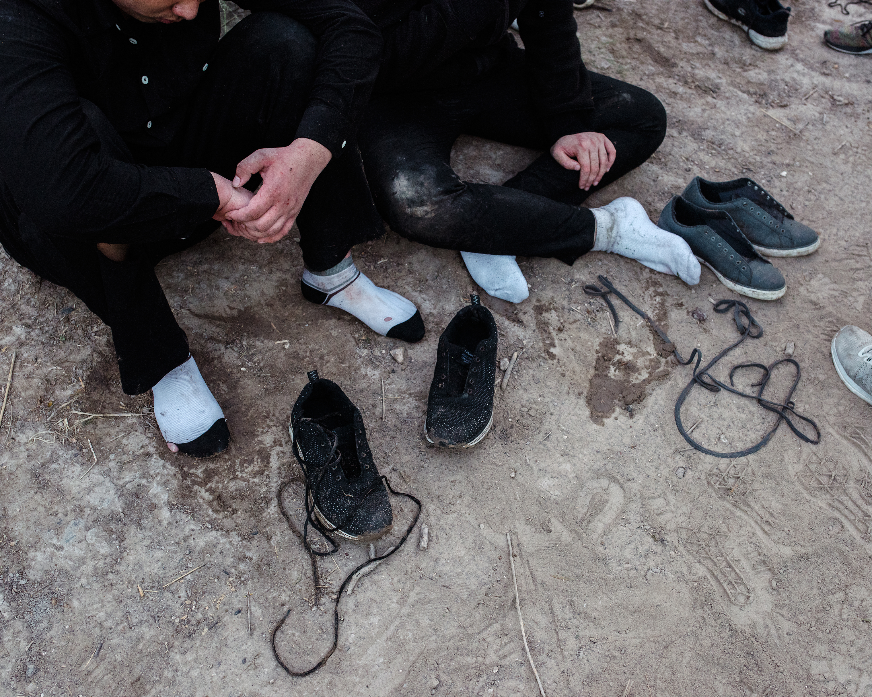 Members of a group of migrants from China and Guatemala unlace their shoes before being taken into custody, after illegally crossing the border through the Rio Grande, on Sept. 25.