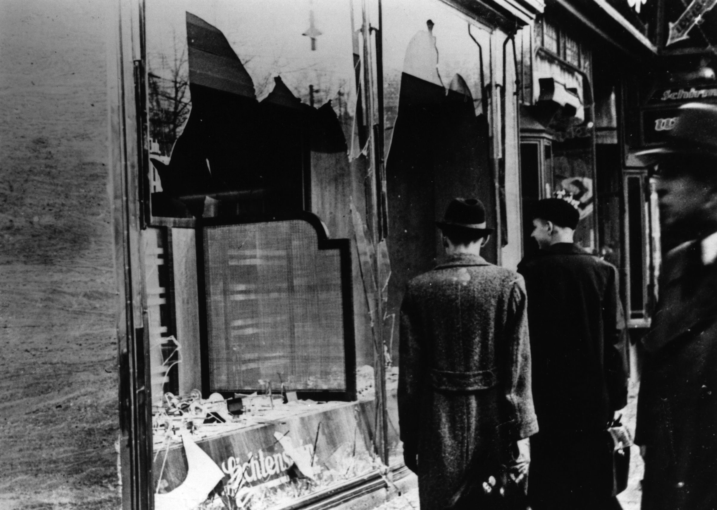 Nov. 10, 1938:  Three onlookers at a smashed Jewish shop window in Berlin following riots of the night of 9th November.