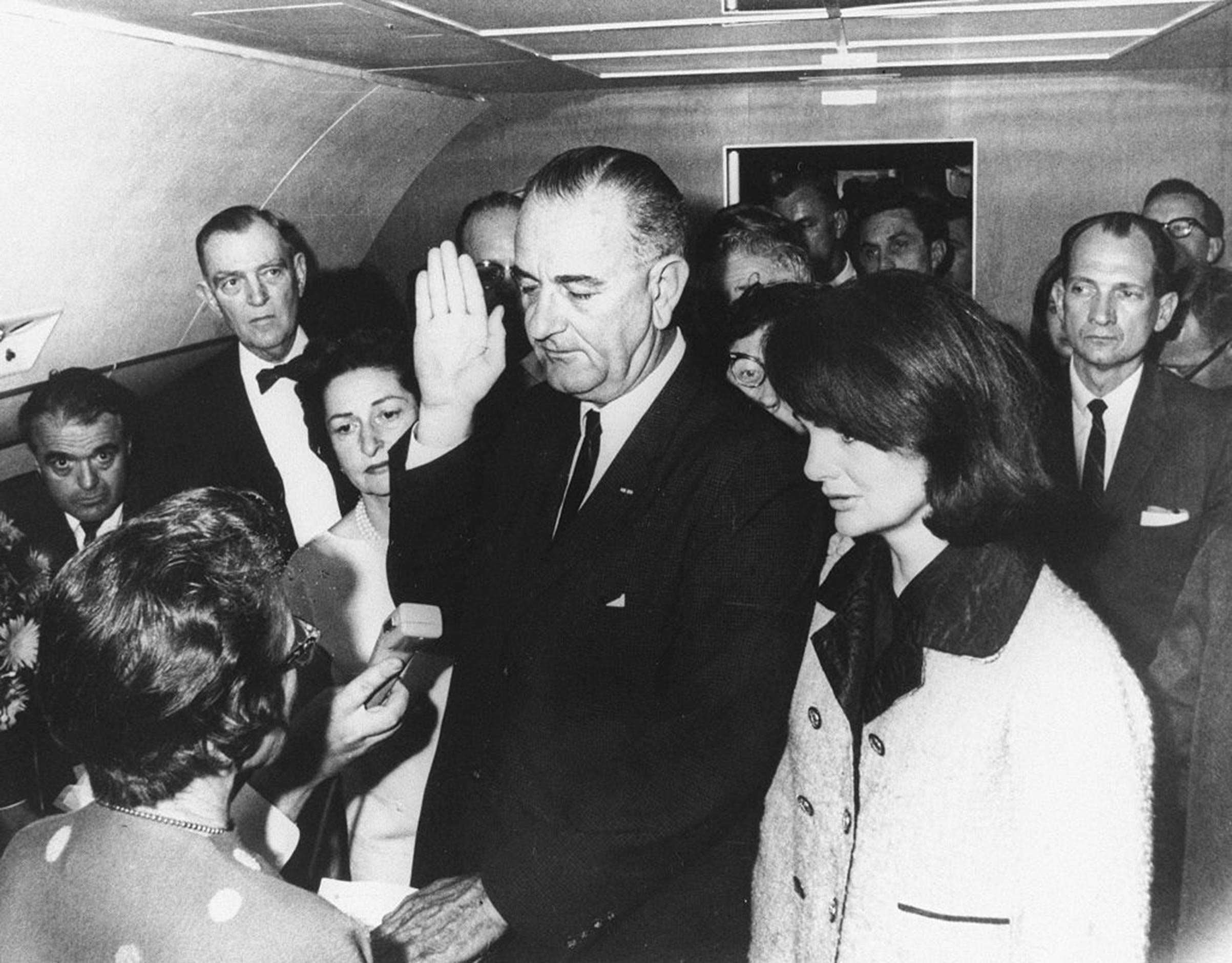 Lyndon B. Johnson is sworn in as President by federal Judge Sarah T. Hughes on Air Force One on Nov. 22, 1963, in Dallas, following the assassination of President John F. Kennedy. He's flanked by Jacqueline Kennedy (right) and wife Lady Bird Johnson (left).