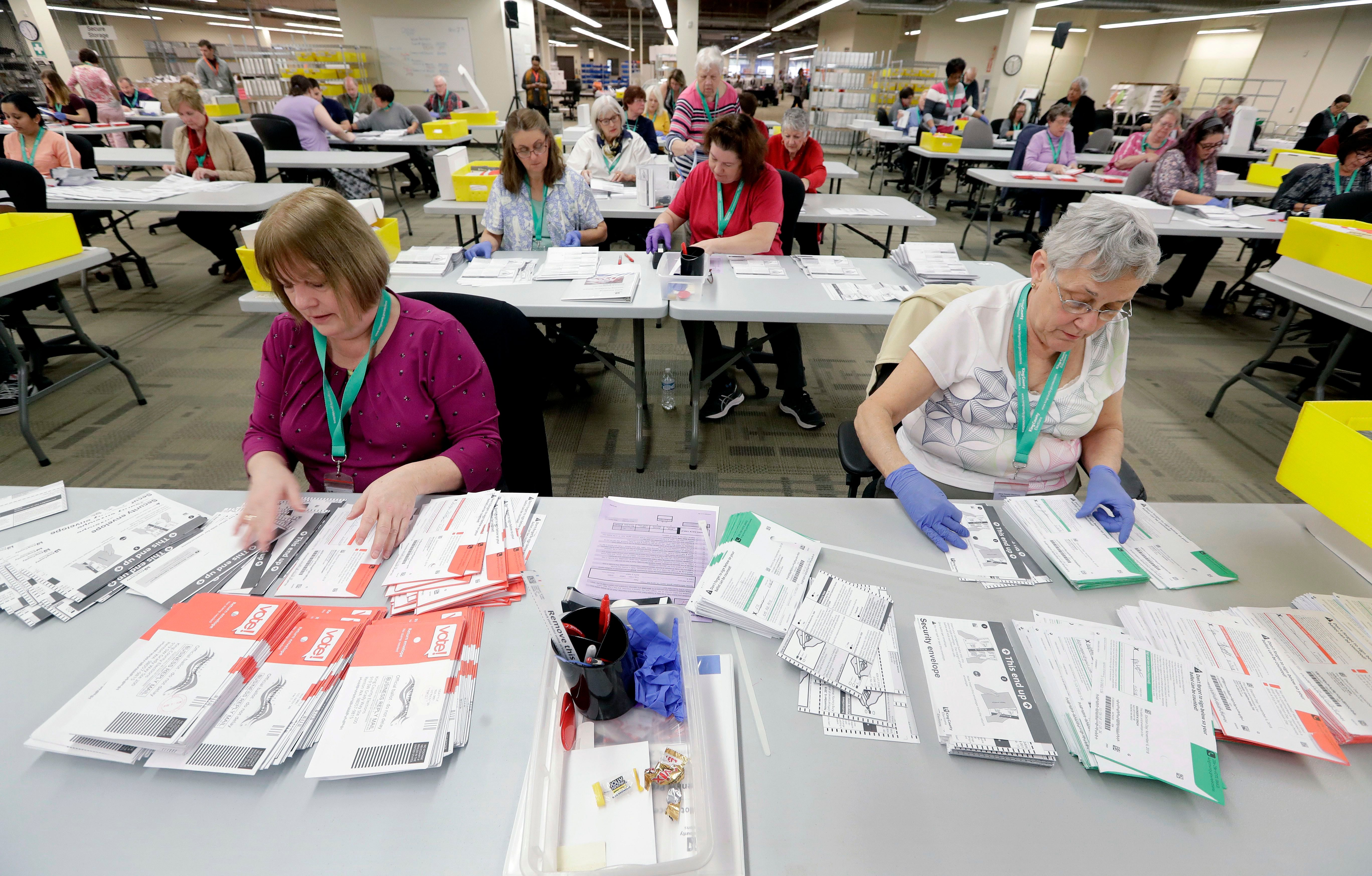 Election workers separate ballots from security envelopes at the King County Elections office, in Renton, Wash., on Nov. 7, 2018.