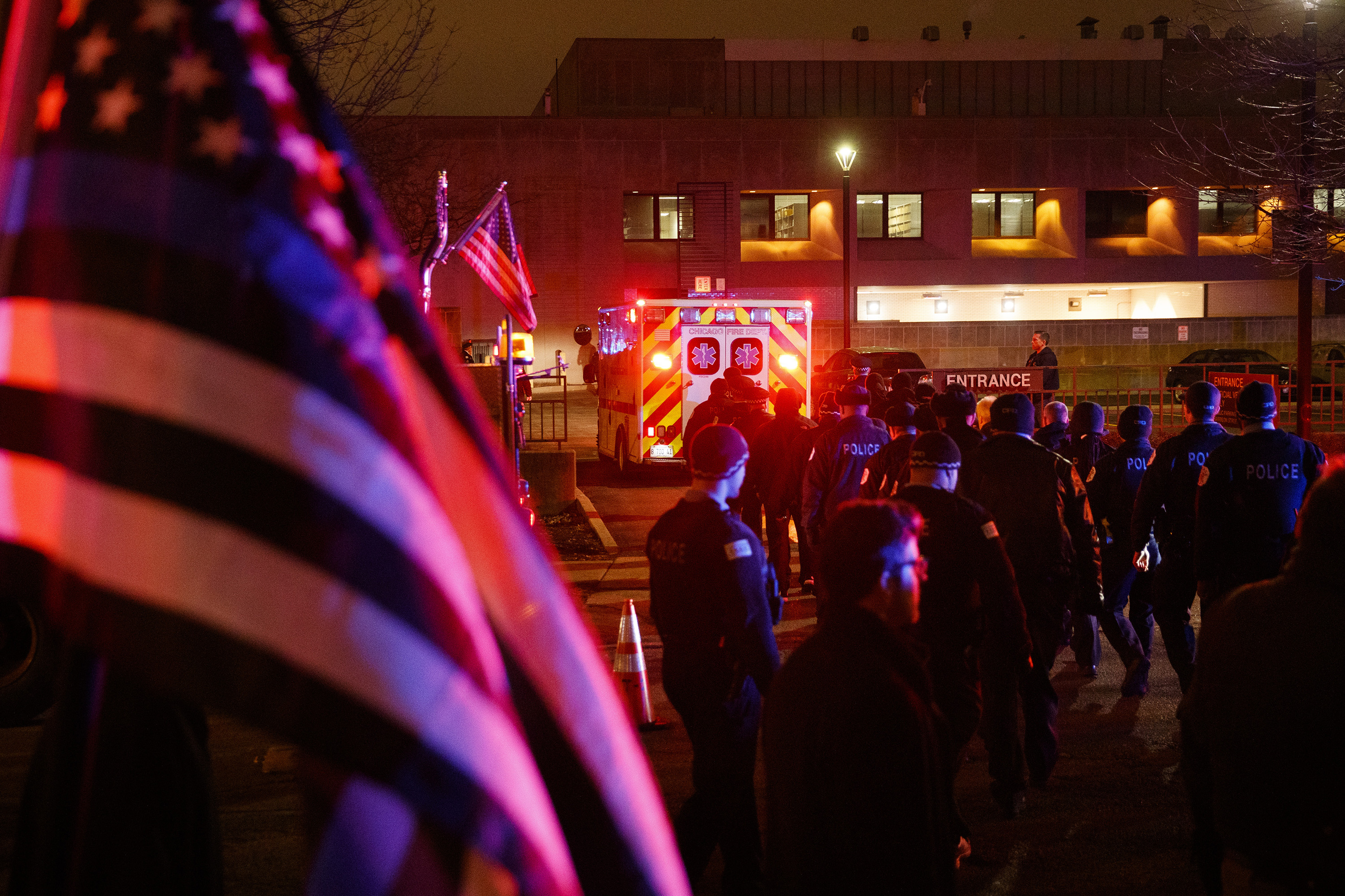 Officers follow an ambulance as it arrives at the medical examiners office carrying the body of a police officer who was killed during a shooting at Mercy Hospital which left four people, including the gunman, dead Monday Nov. 19, 2018 in Chicago. (Armando L. Sanchez/Chicago Tribune/TNS via Getty Images)