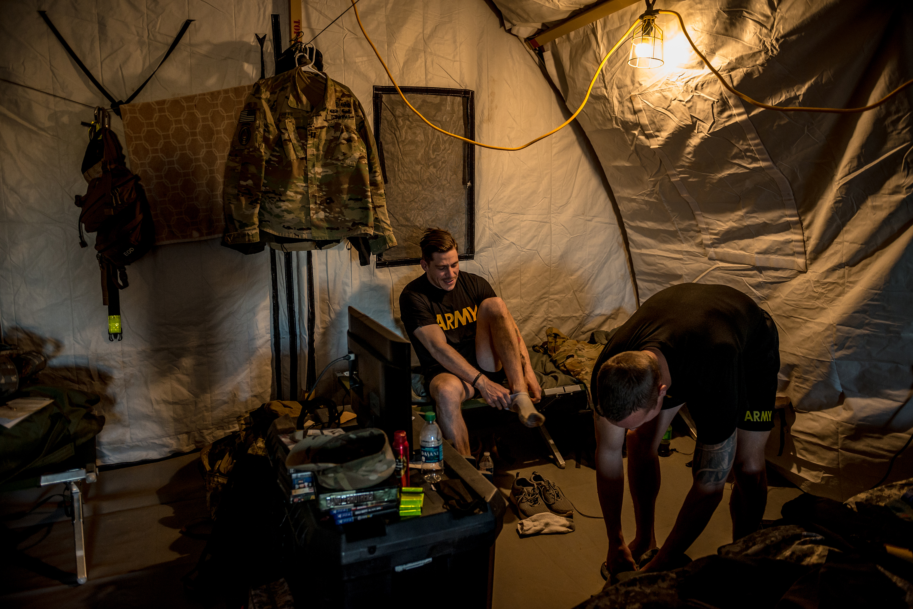 Cpt. Jacob Riffe, 29, from Augusta, Ga., puts his shoes on after waking up just after dawn inside his unit's tent.