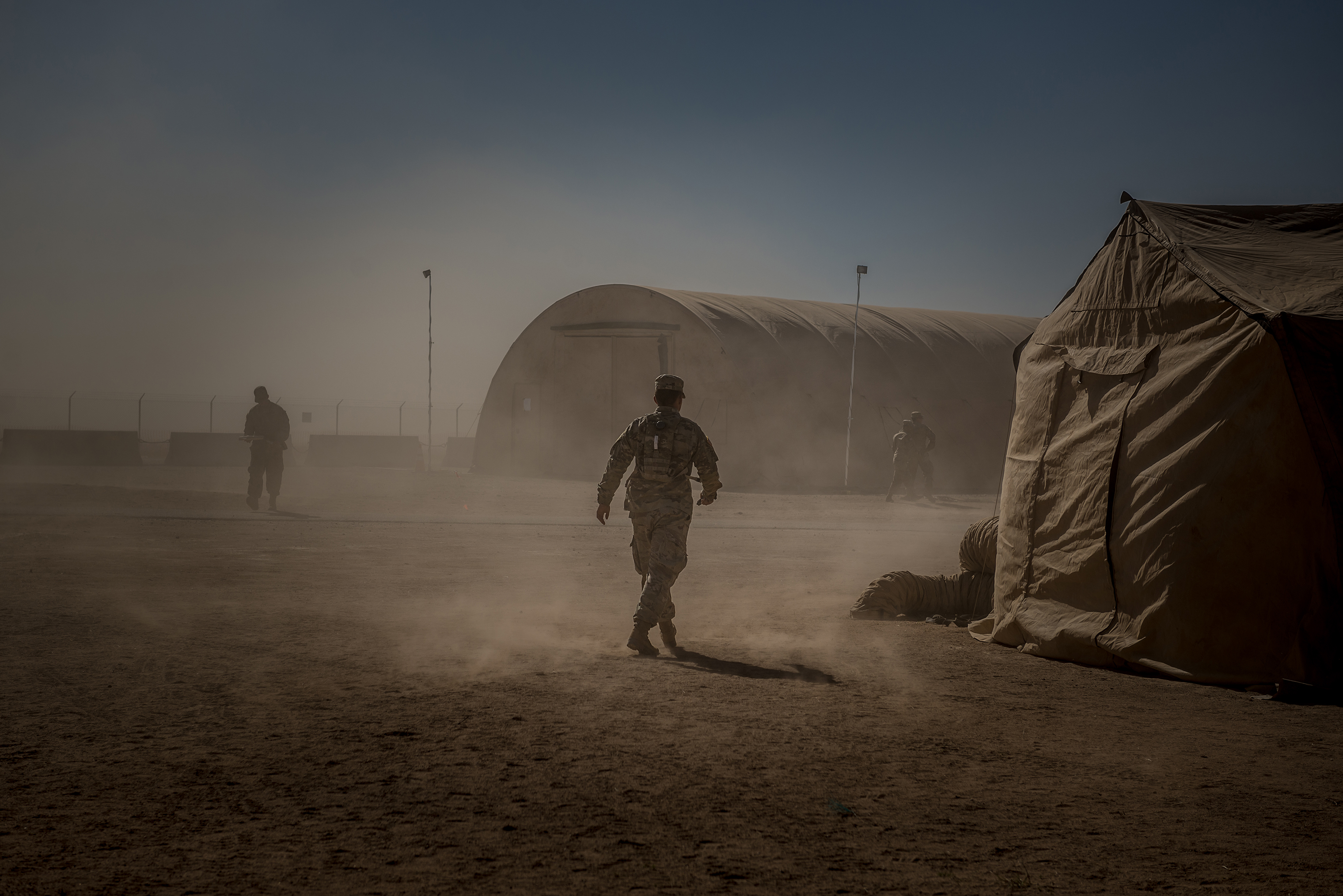 A soldier walks through a sandstorm at Sunglow City.