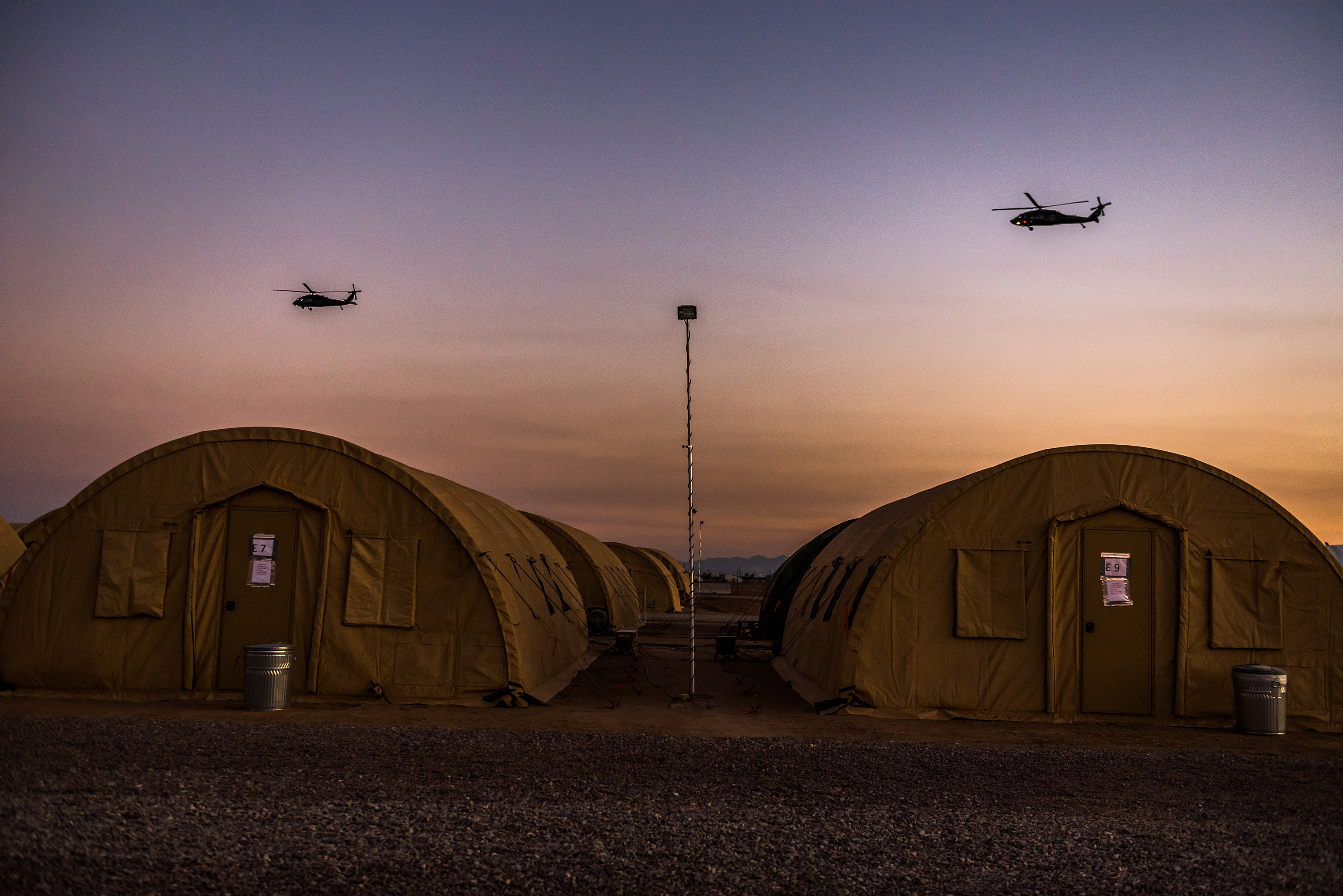 Helicopters fly over rapidly assembled tents used for army sleeping quarters.