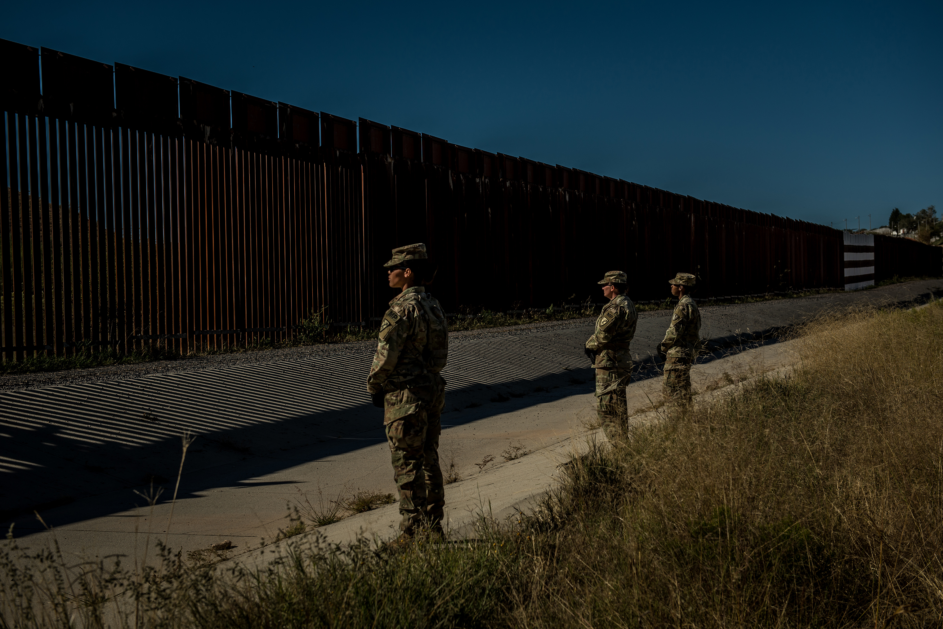 Soldiers of the 104th Engineer Construction Company stand guard as other members of their unit work to heighten security of the border wall.