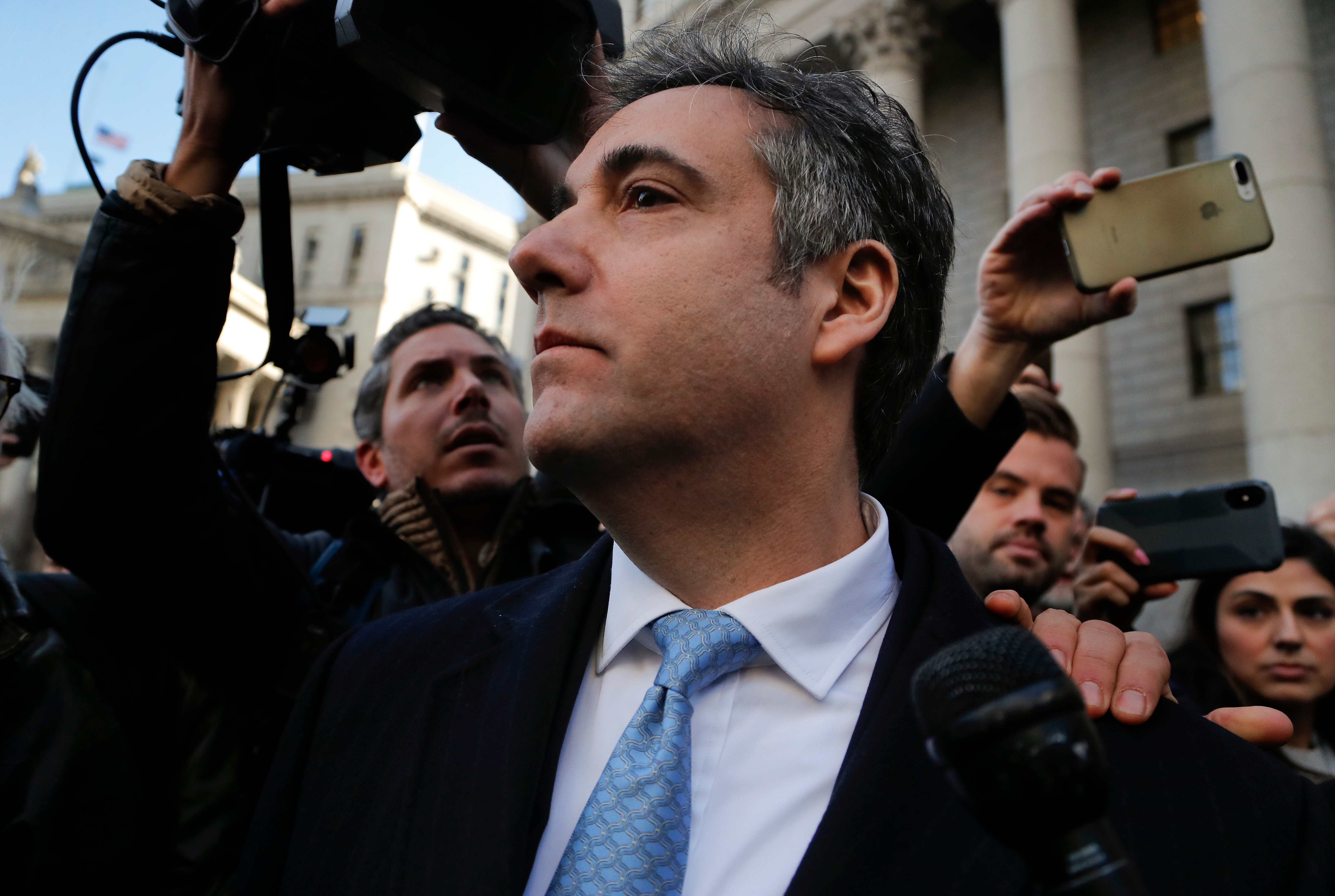 Michael Cohen walks out of federal court, in New York, after pleading guilty to lying to Congress about work he did on an aborted project to build a Trump Tower in Russia, on Nov. 29, 2018.