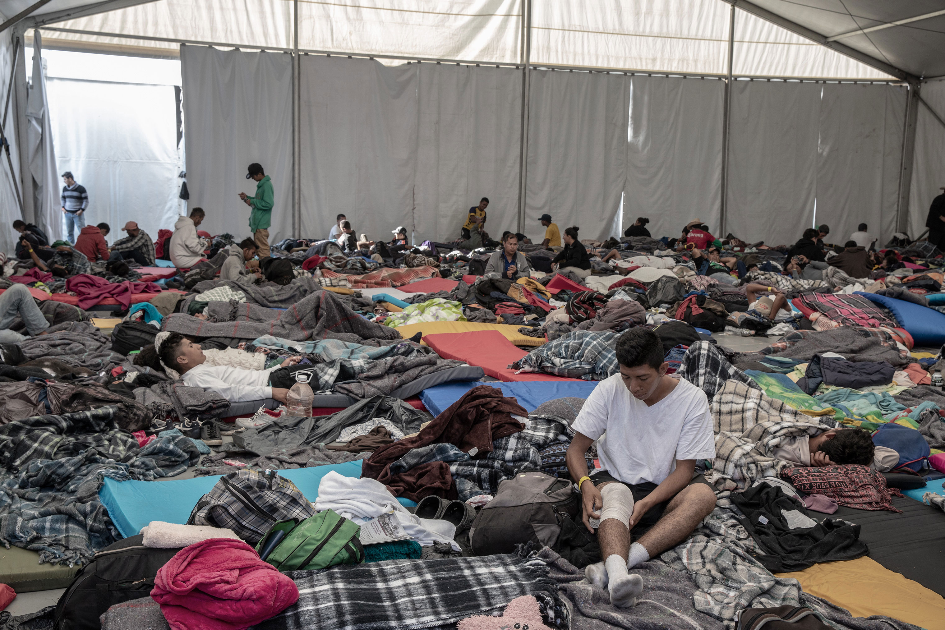Migrants waking up inside one of the several tents that volunteers set up inside the Jesus Martinez stadium in Mexico City, Nov. 7, 2018.