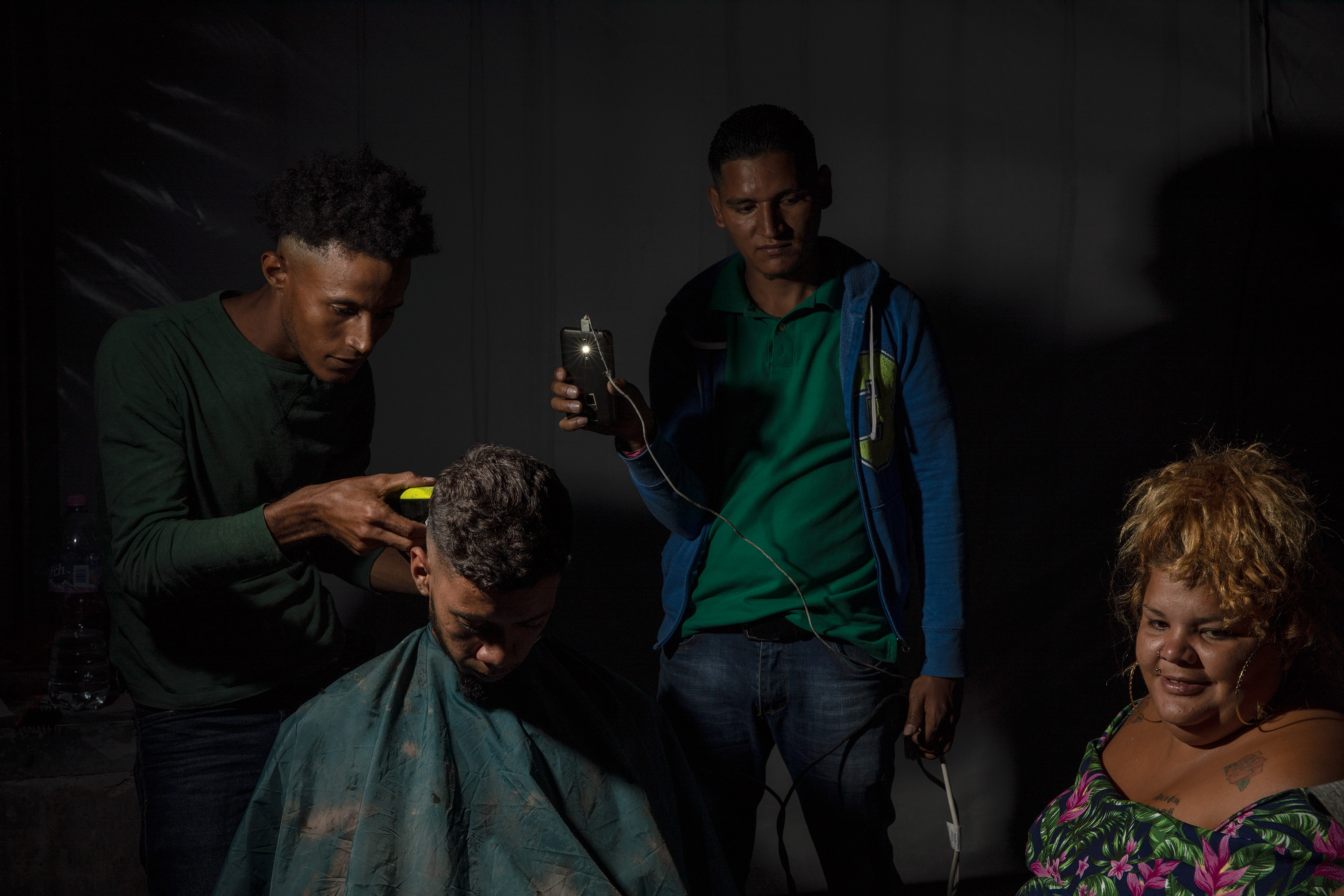 Ayyi Collins, 23, is a barber from Roatán, Honduras at the Jesus Martinez stadium on Nov. 7, 2018. He and his wife left Honduras, where he was a taxi driver, because of the terrible economy. He charges 30 pesos ($1.50) to people in the caravan for a haircut. He said,  You shouldn't believe that everyone here is a bad person. We want to find a better life and we want new opportunities to change the course of history.
