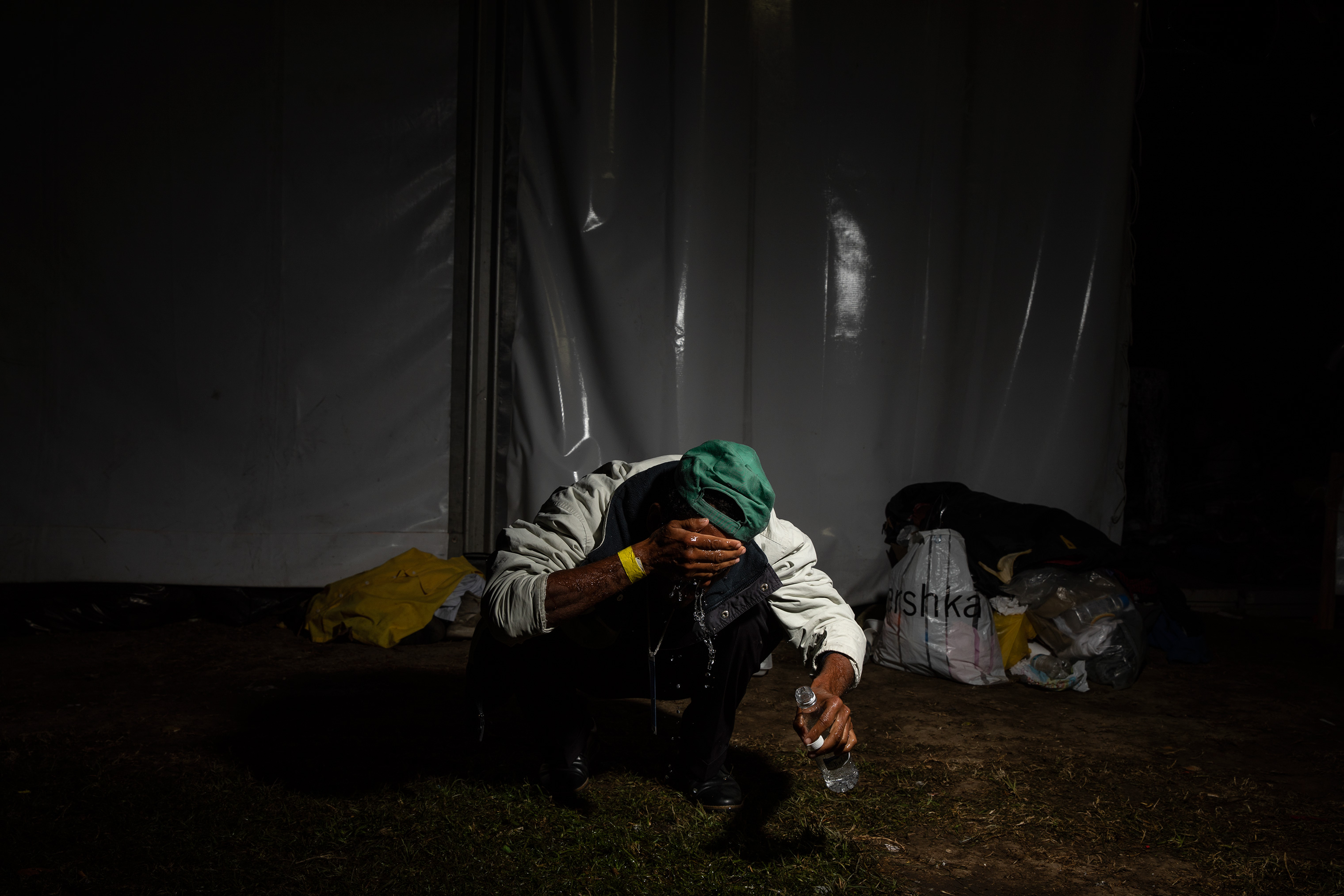 A migrant washes his face with bottled water outside of the tent where he will sleep at the Jesus Martinez stadium, on Nov. 9 2018.