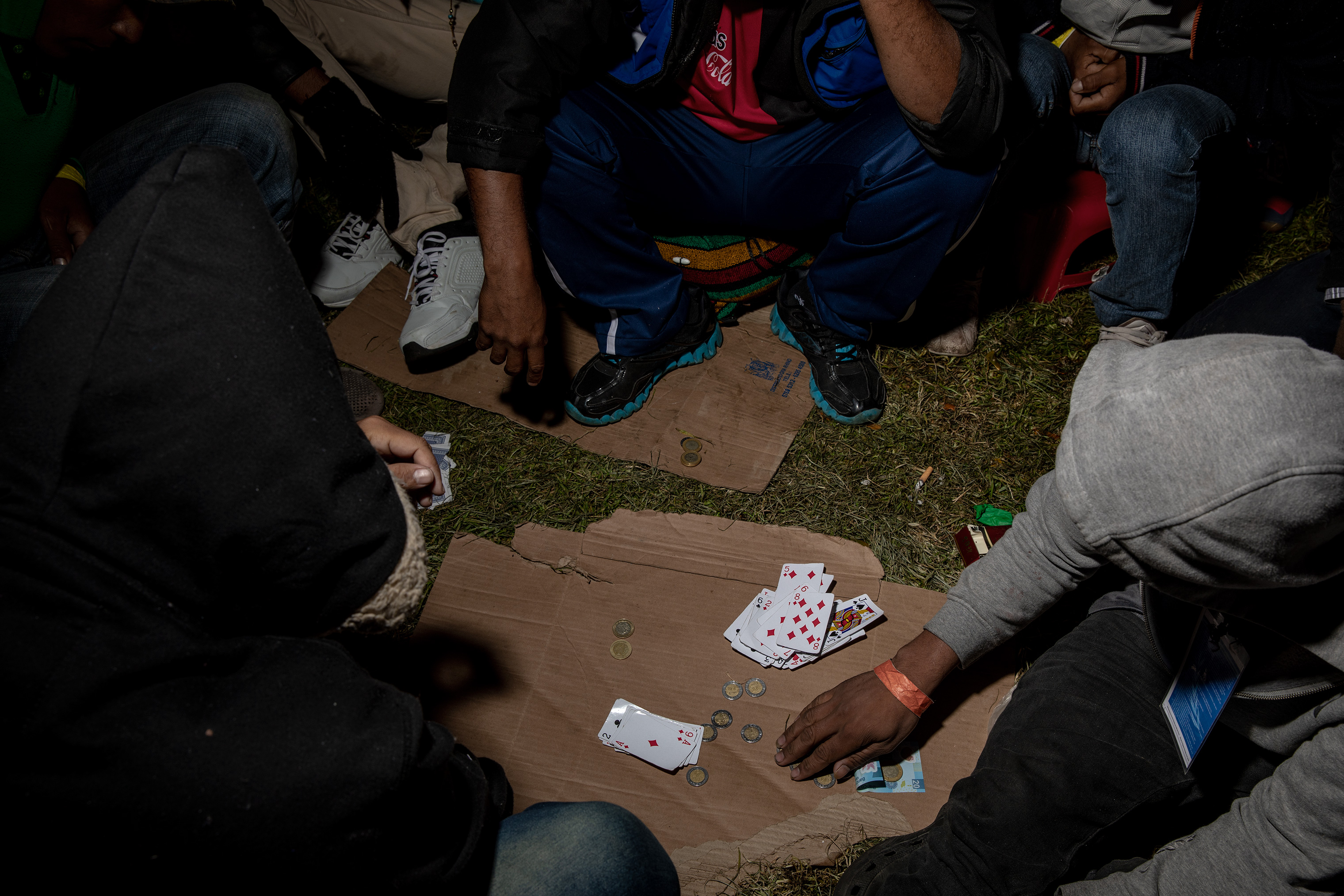 To pass the time at the stadium, migrants play cards, Nov. 9, 2018.