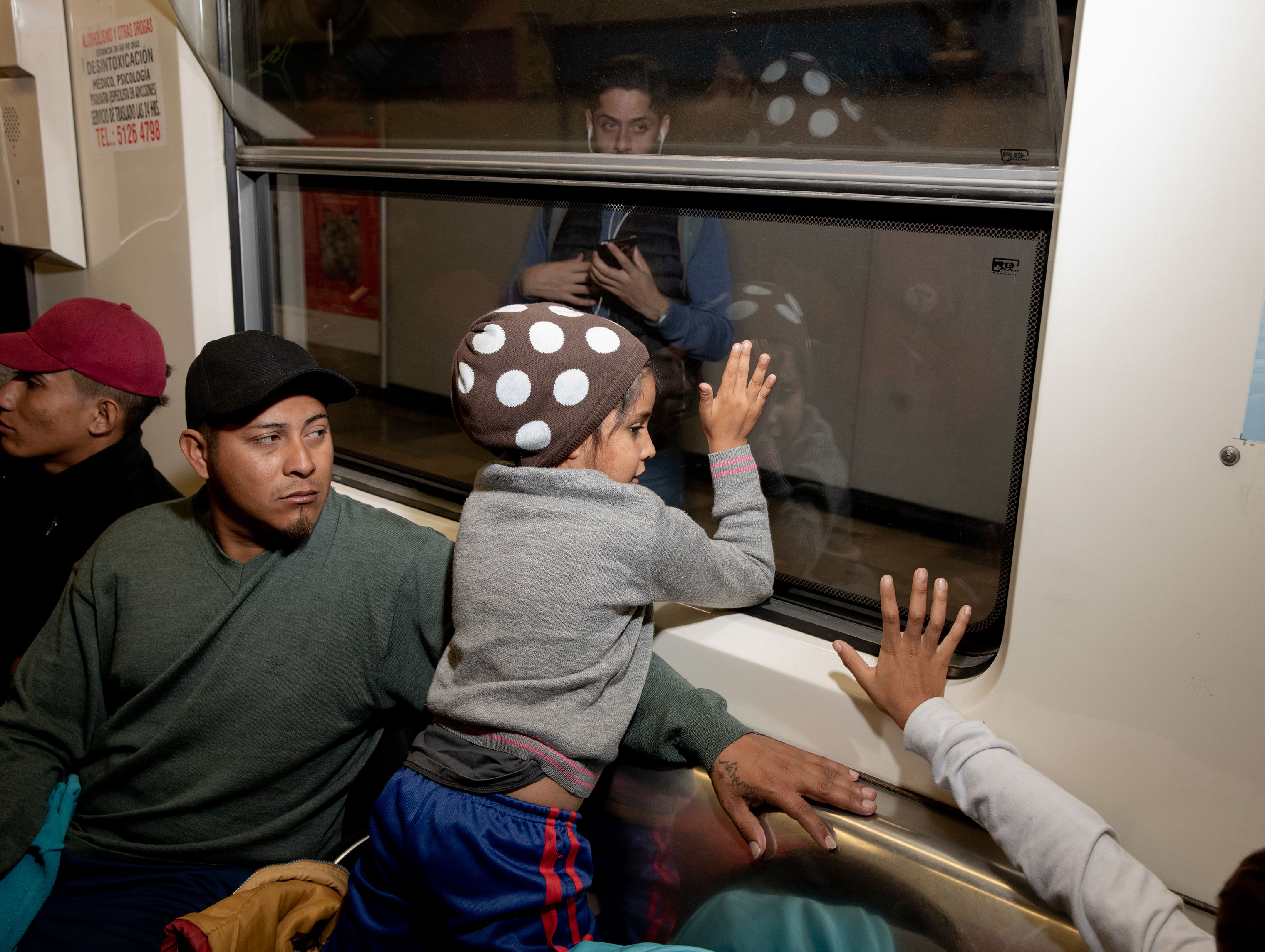 The migrant caravan exited Mexico City on the metro on the morning of Nov. 10, 2018. A young girl waves to a woman on the other side of the metro car.