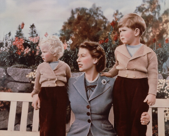 Queen Elizabeth II with Prince Charles and Princess Anne in the grounds of Balmoral Castle, Scotland. Charles is celebrating his 4th birthday.