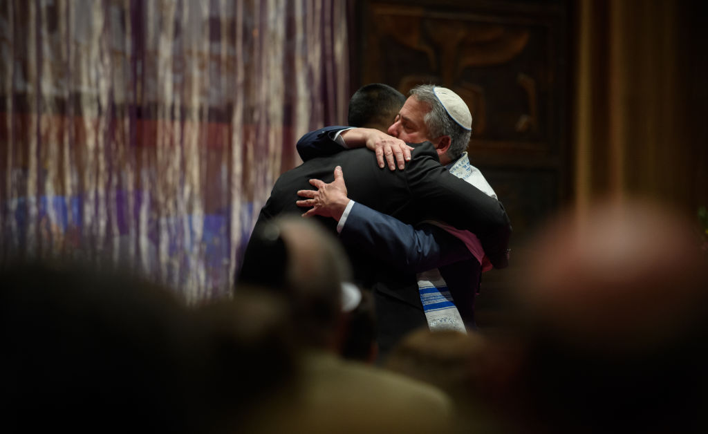 Rabbi Jamie Gibson and Wasi  Mohamed, Director of the Islamic Center of Pittsburgh, embrace in the sanctuary at Temple Sinai for Friday evening Shabbat services on November 2, 2018 in Pittsburgh, Pennsylvania.