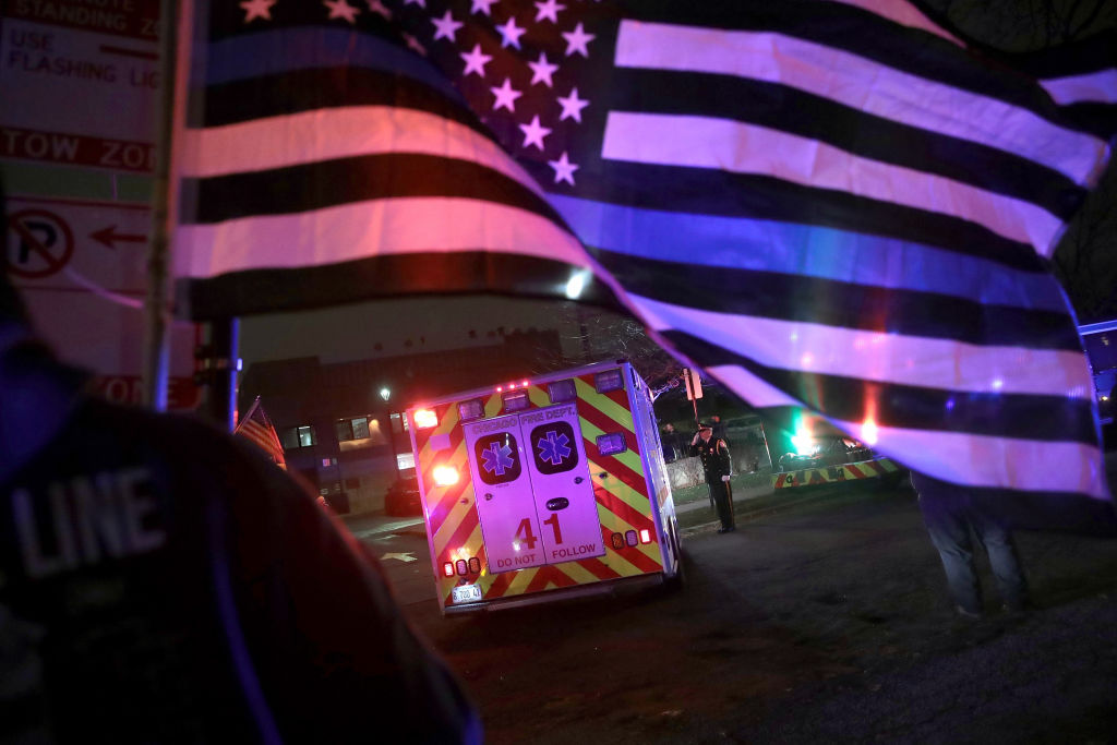 Police and firefighters follow the ambulance carrying the remains of Chicago Police officer Samuel Jimenez as it arrives at the Cook County Medical Examiner's office   on November 19, 2018 in Chicago, Illinois.