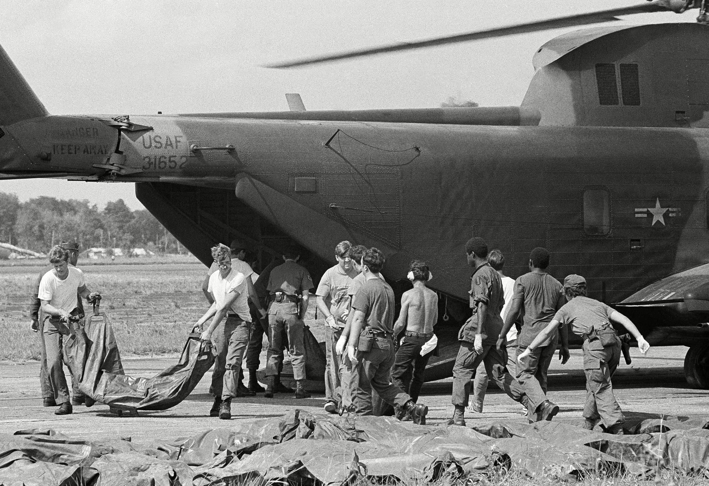 Bodies of victims of Jonestown mass suicide are loaded from U.S. military helicopter at Georgetown's international airport. The corpses, in body bags, will be transferred to shipping containers for the flight back to the U.S.