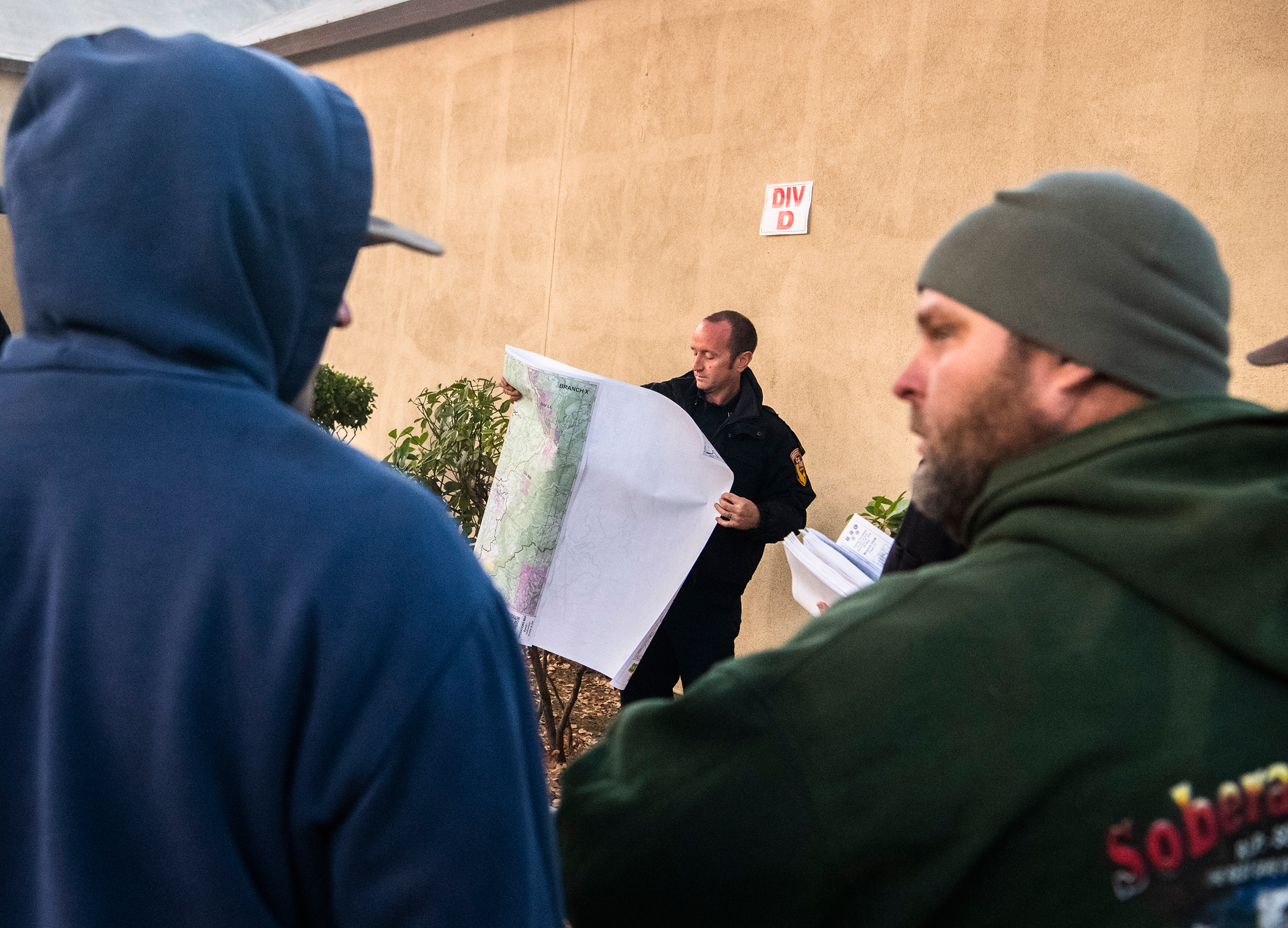 A firefighter unfurls a map for the division Delta briefing at the Camp Fire incident command post on Nov. 20, 2018.
