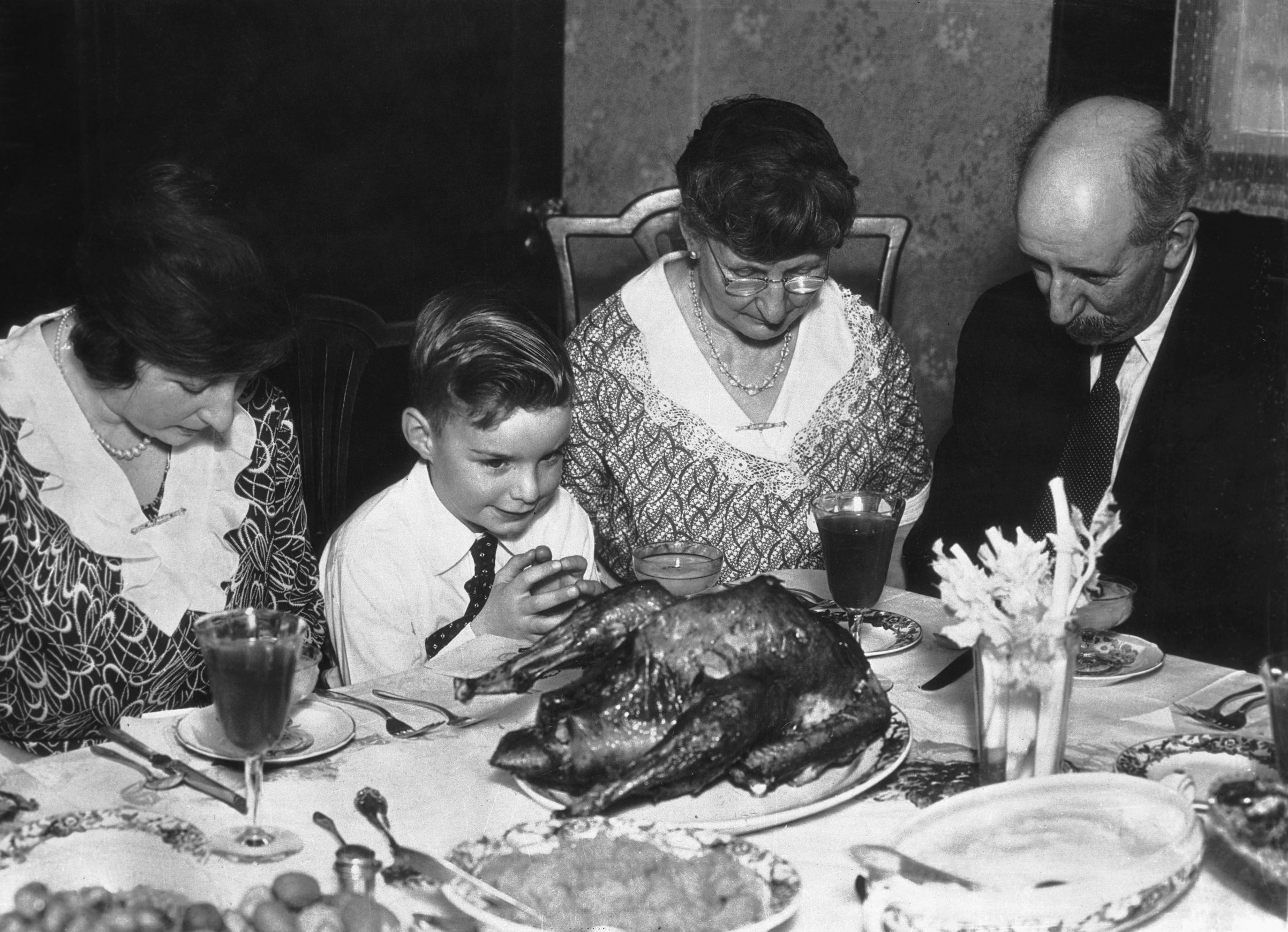 A family saying grace before Thanksgiving dinner. Ca. 1930s.