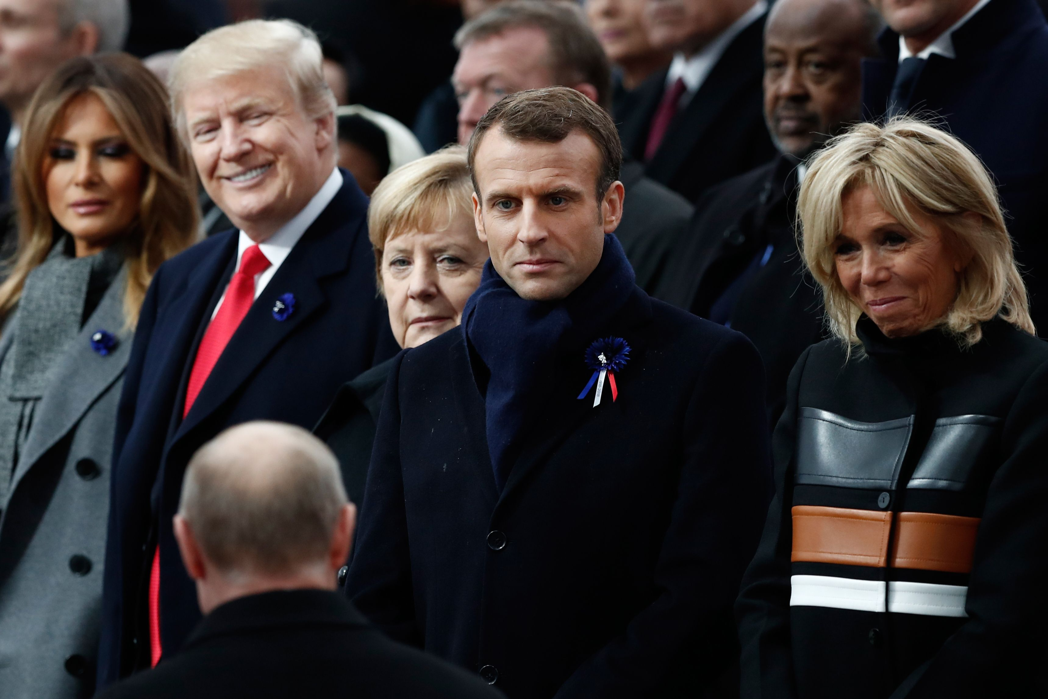 US First Lady Melania Trump, US President Donald Trump, German Chancellor Angela Merkel, French President Emmanuel Macron and French President's wife Brigitte Macron react as Russian President Vladimir Putin (front C) arrives to attend a ceremony at the Arc de Triomphe in Paris on November 11, 2018.