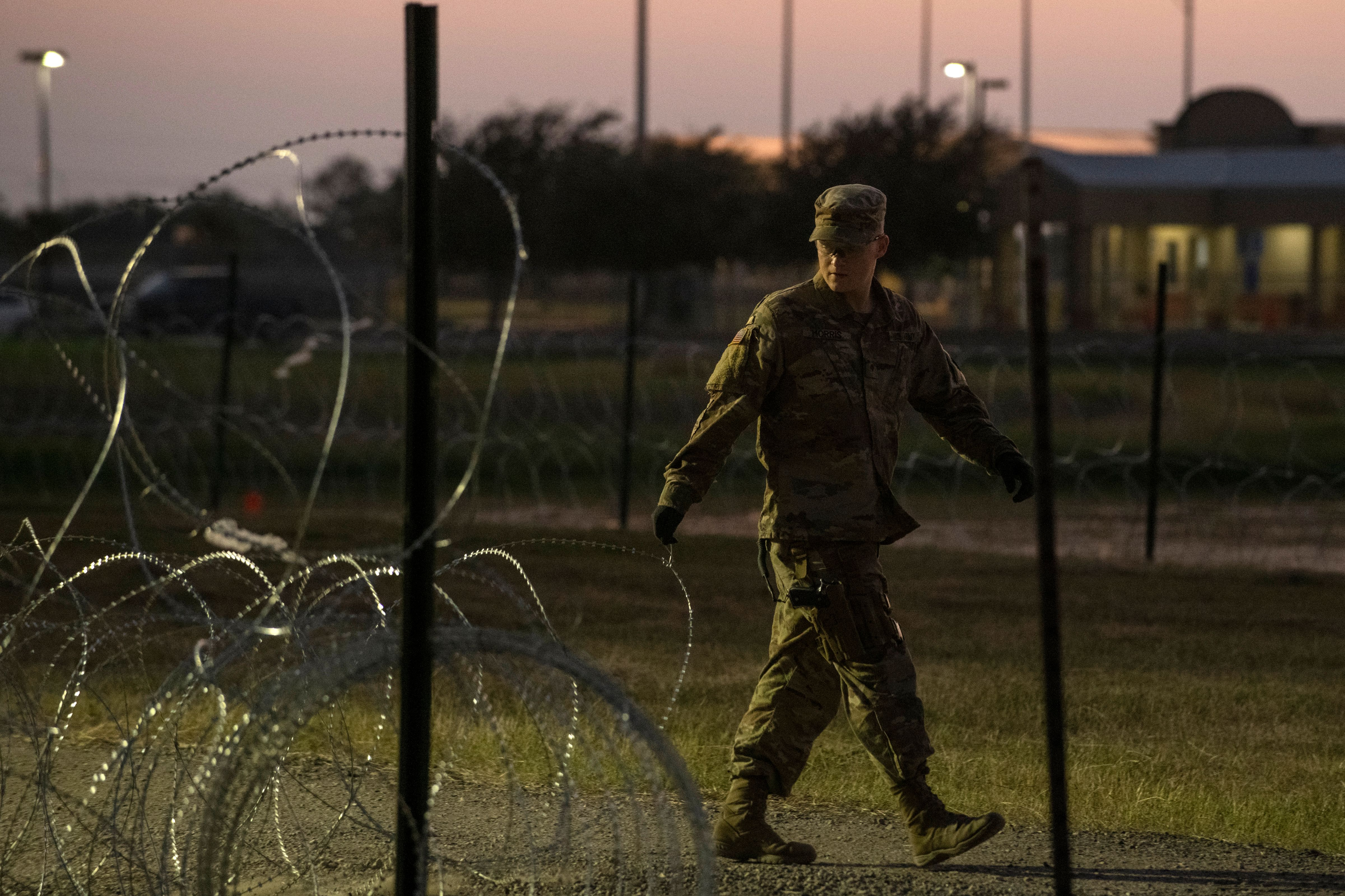 A US Army soldier closes a razor-wire gate at a compound where the military is erecting an encampment near the US-Mexico border crossing at Donna, Texas, on November 6, 2018.