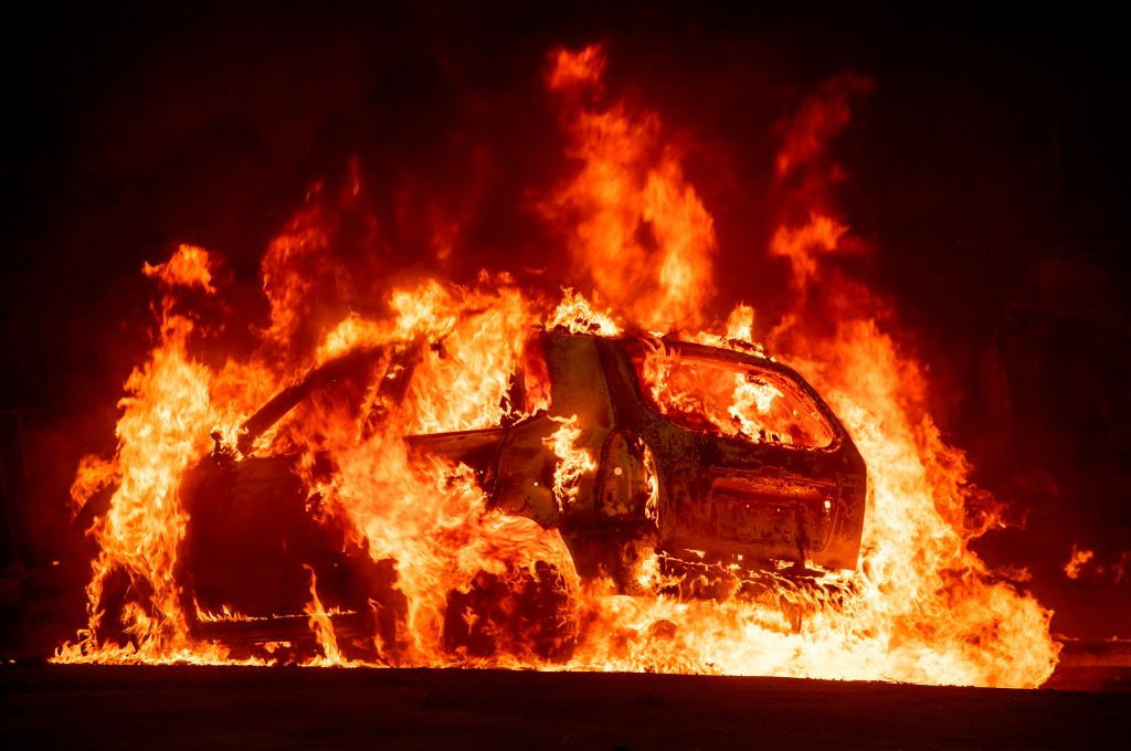 A car explodes into flames as the Camp fire tears through downtown Paradise, California on November 8, 2018. 5 people were confirmed dead in a vehicle torched by the wildfire on Nov. 9, 2018.