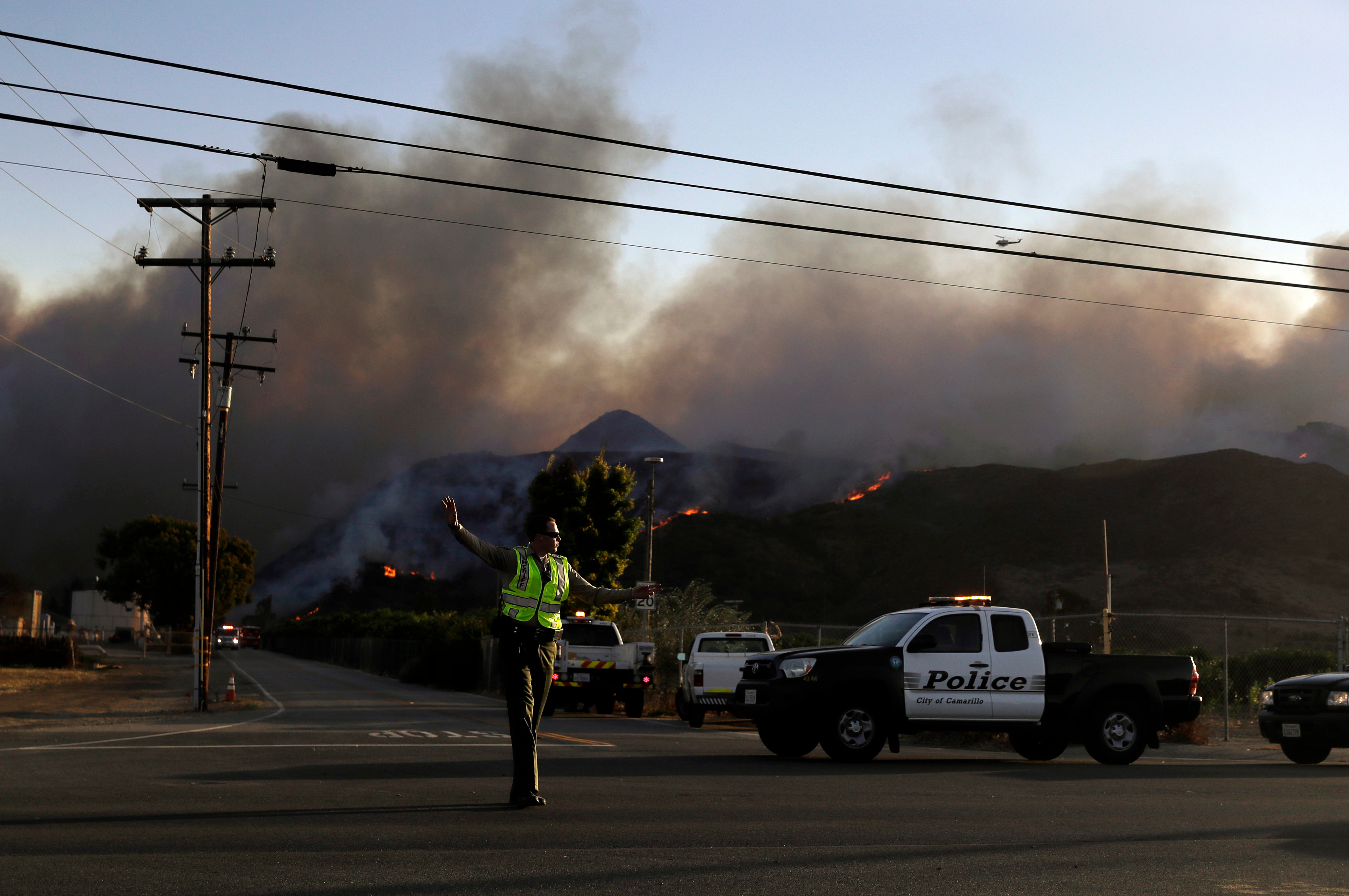 A police officer mans a checkpoint in front of an advancing wildfire, near Newbury Park, Calif. onNov. 9, 2018. The Ventura County Fire Department has also ordered evacuation of some communities in the path of the fire, which erupted a few miles from the site of Wednesday night's deadly mass shooting at a Thousand Oaks bar.