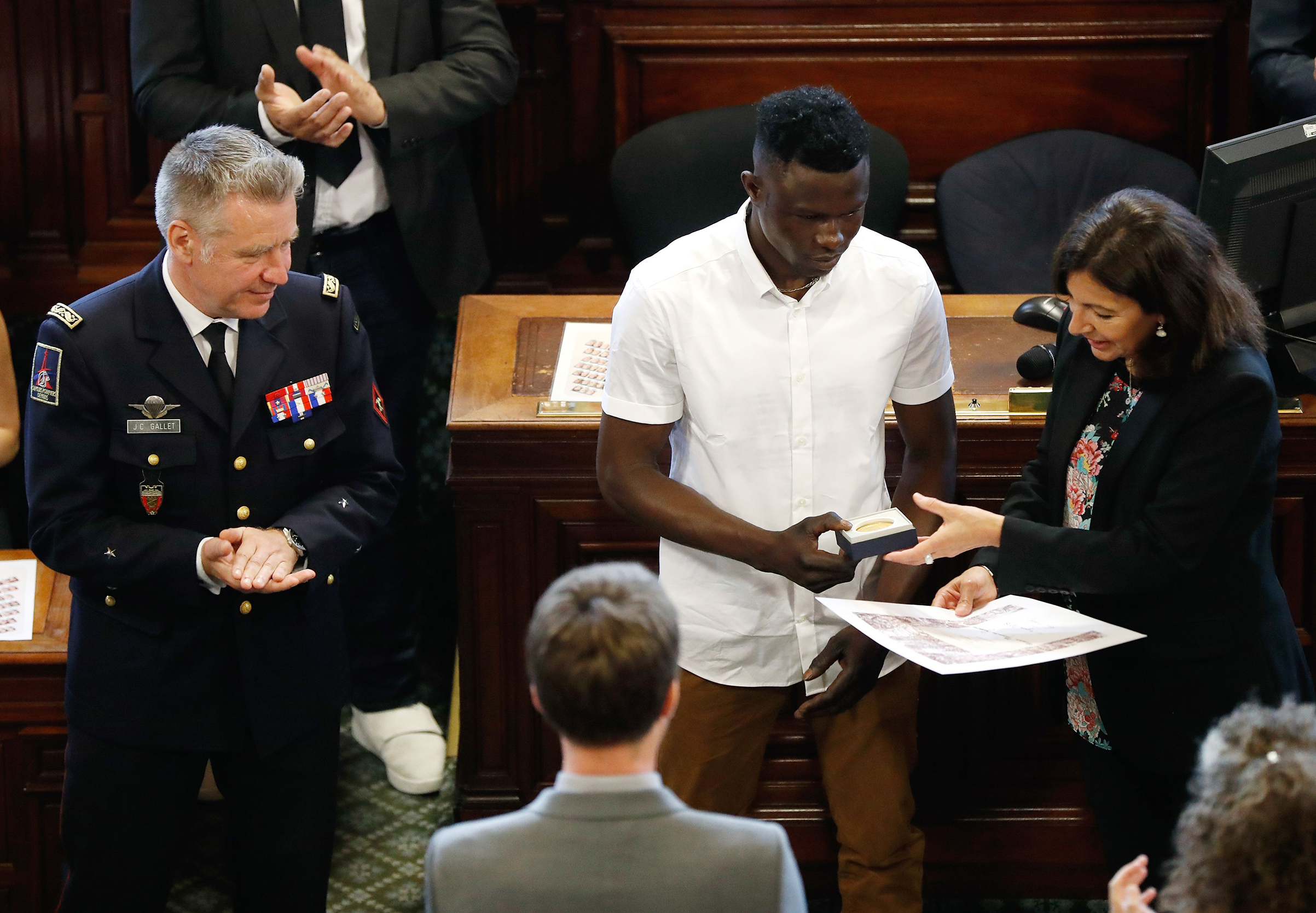 Mamoudou Gassama, center, is awarded with the city's Grand Vermeil medal by Paris' mayor Anne Hidalgo in Paris on June 4, 2018.
