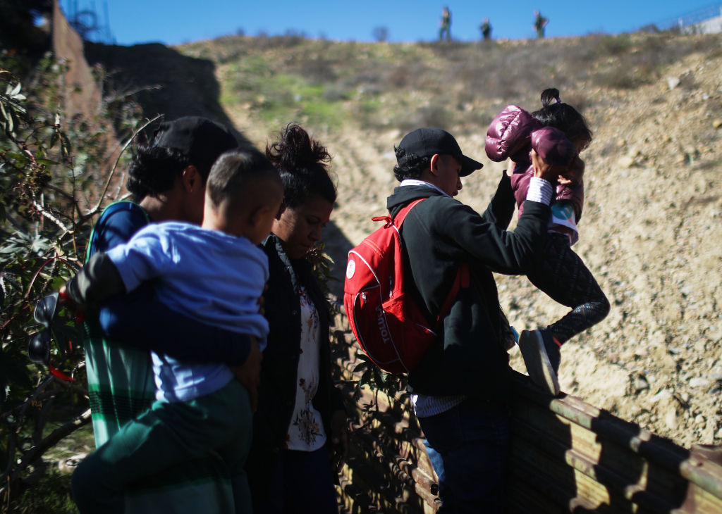 Migrants from Central America cross the U.S.-Mexico border fence before turning themselves in to the U.S. Border Patrol on December 16, 2018 in Tijuana, Mexico.