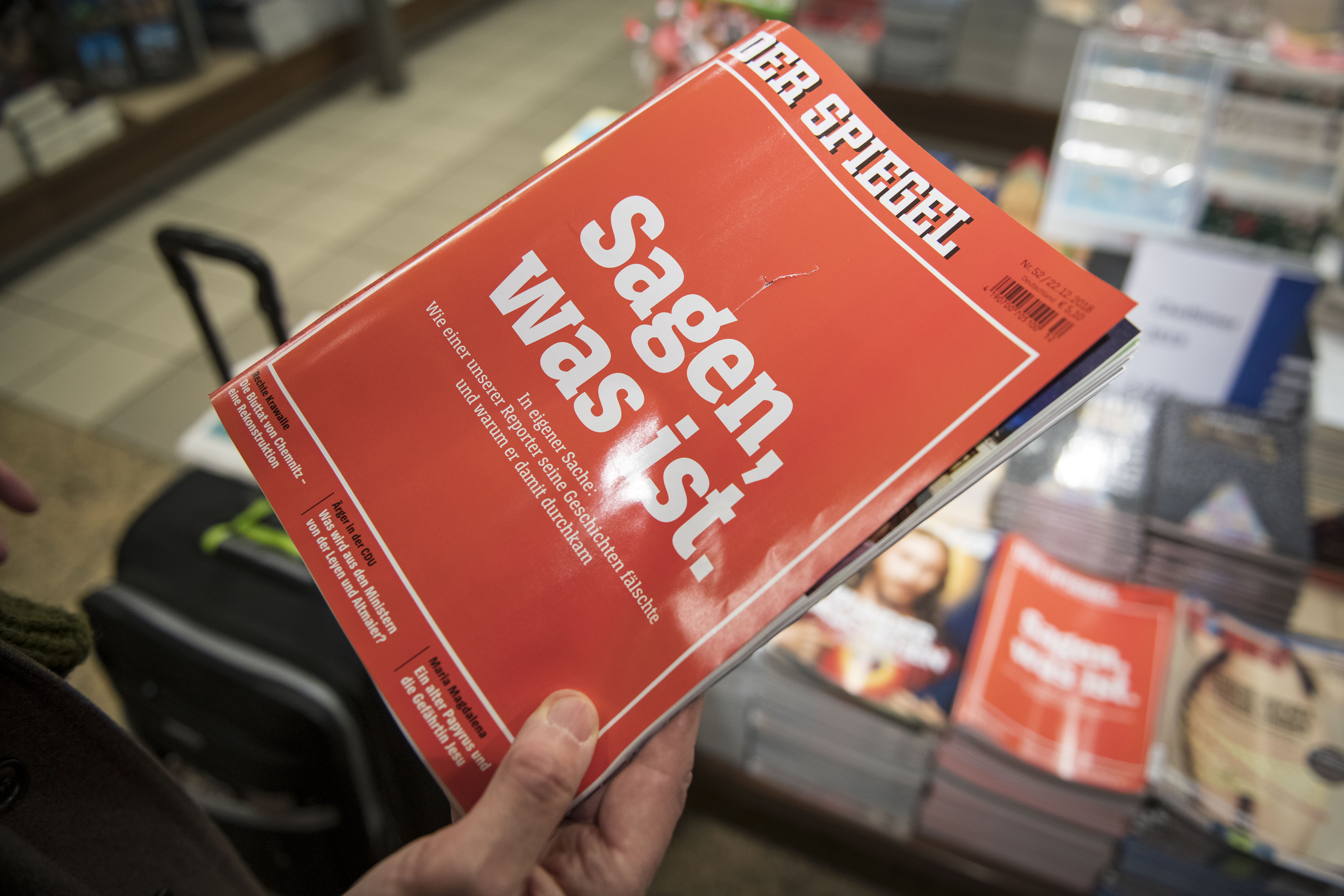 A man holds the latest issue of German newsweekly Der Spiegel with a cover page that reads:  To say, what is  at a kiosk in Cologne, Germany on Dec. 22, 2018.