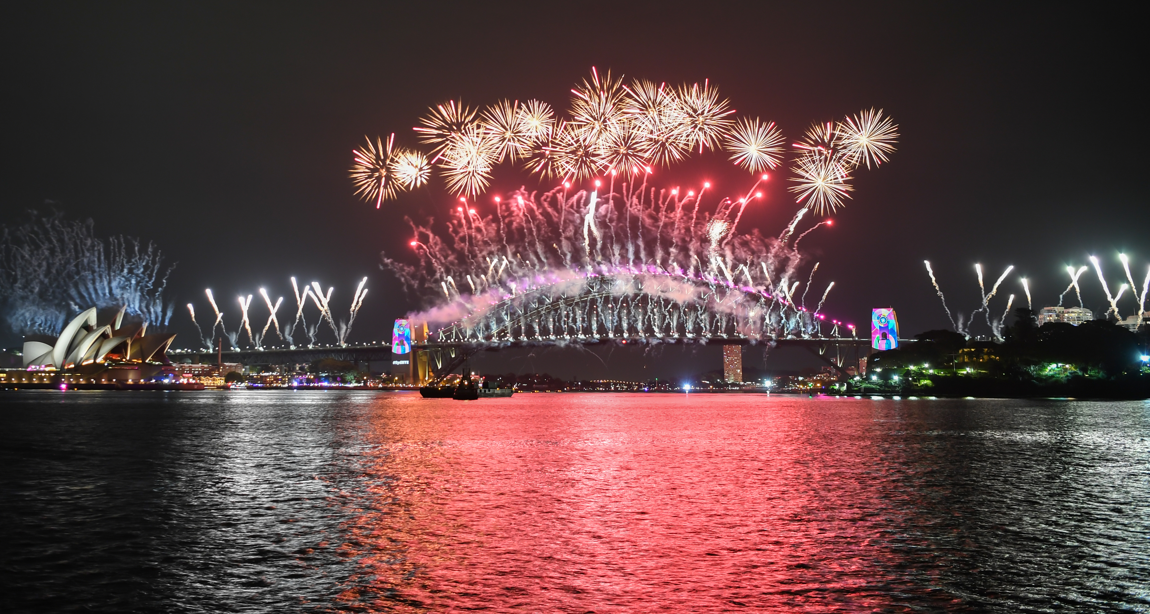 SYDNEY, AUSTRALIA - JANUARY 01: The Sydney Harbour Bridge is bathed in fireworks and lighting effects during New Year's Eve celebrations on January 1, 2019 in Sydney, Australia. (Photo by James D. Morgan/Getty Images)