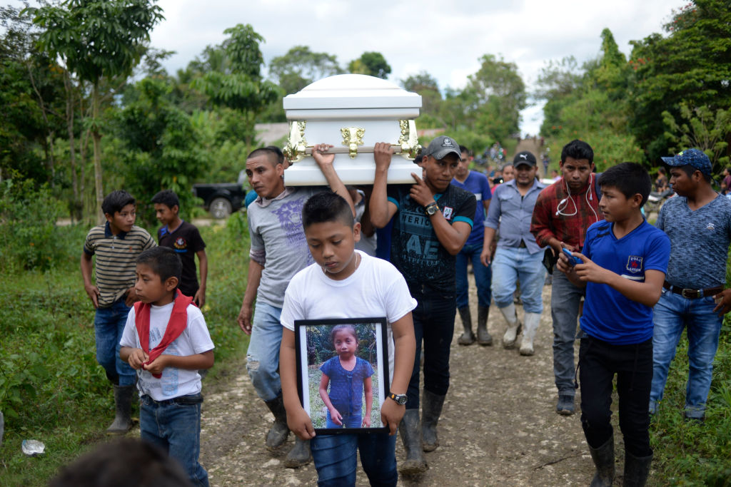 A boy carries a picture of Guatemalan seven-year-old Jakelin Caal, who died in a Texas hospital two days after being taken into custody by US border patrol agents in a remote stretch of the New Mexico desert.