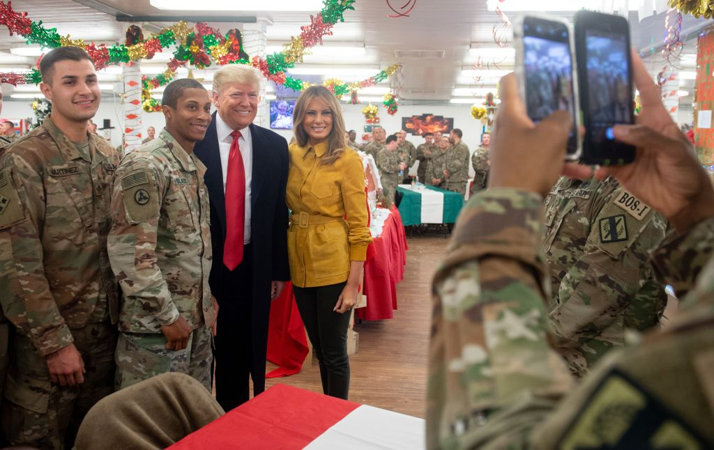 US President Donald Trump and First Lady Melania Trump take photos with members of the US military during an unannounced trip to Al Asad Air Base in Iraq on December 26, 2018.