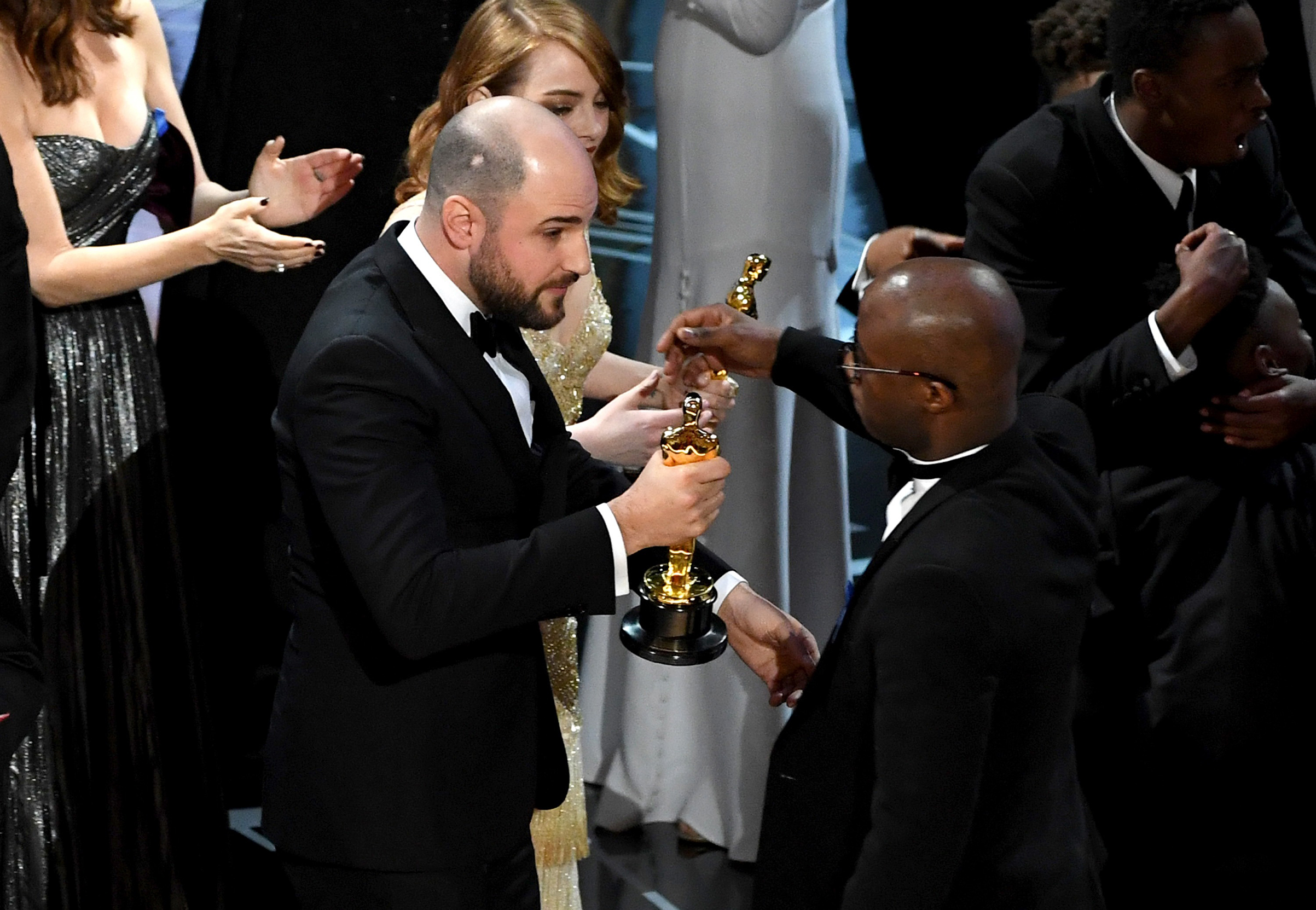 La La Land producer Jordan Horowitz hands a stunned Jenkins the Best Picture statue at the 2017 Oscars