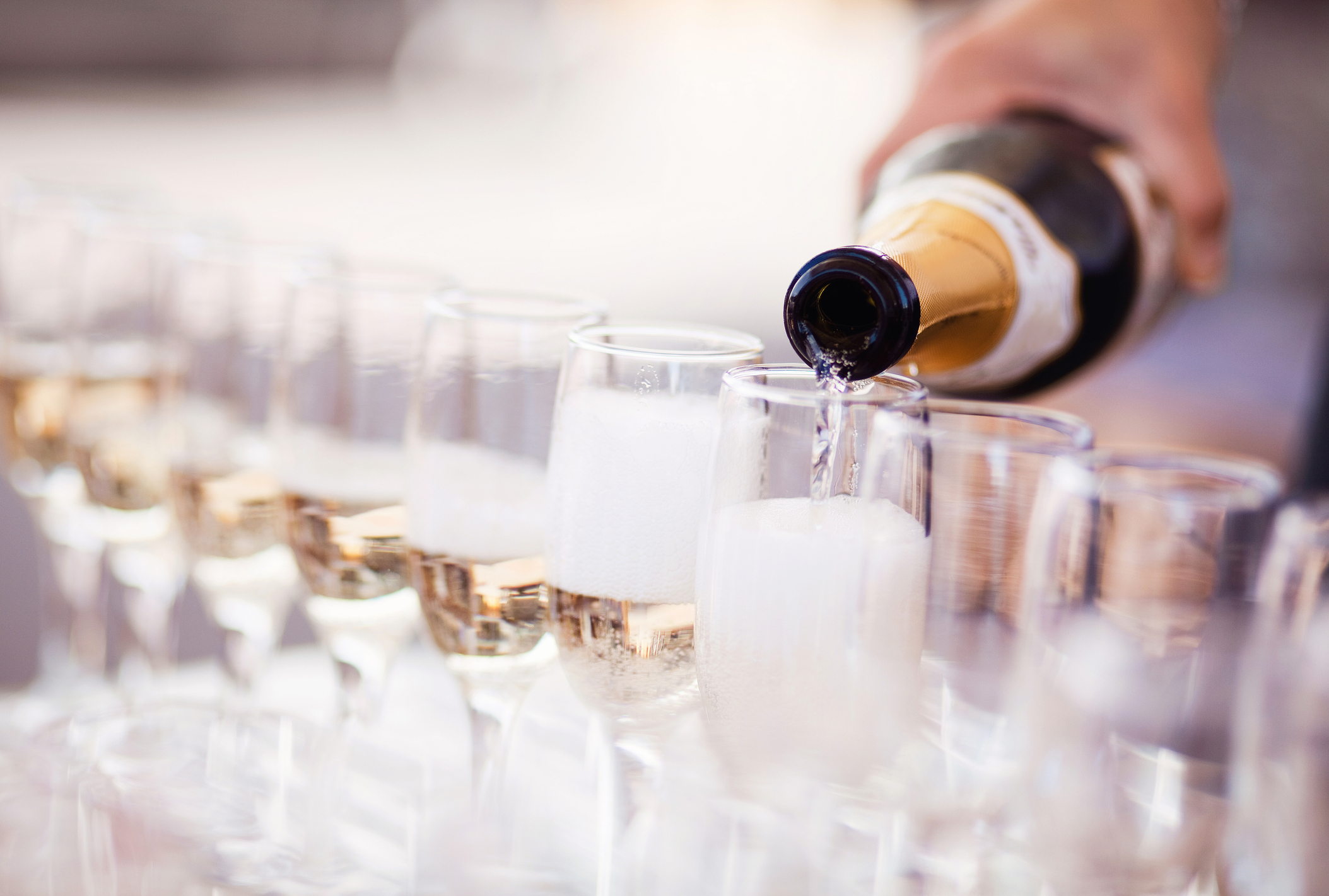 Waiter serving a glass of sparkling white wine