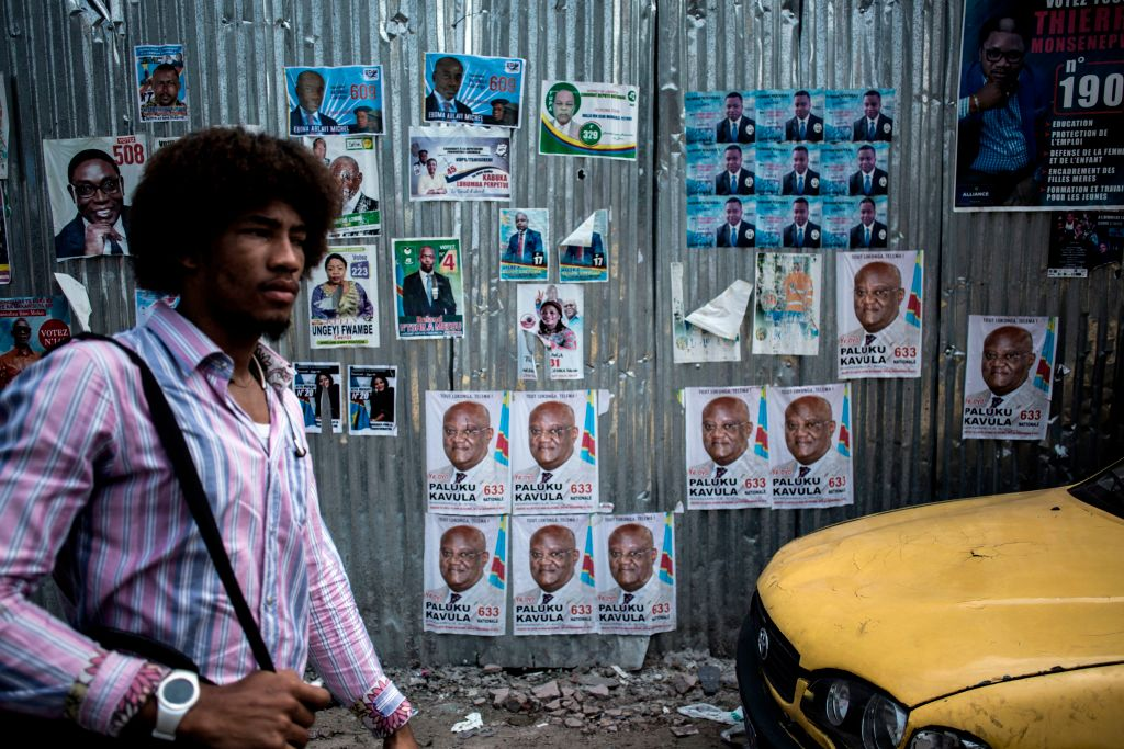 A man walks past a wall filled with campaign posters in the district of Lingwala in Kinshasa on December 18, 2018.  Democratic Republic of Congo goes to the polls in December 2018 in elections that could see the country emerge from 17 years of conflict-ridden rule under controversial President Joseph Kabila.