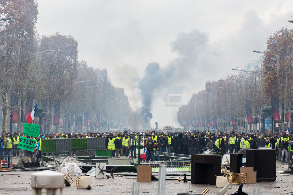 Protestors stand in front of the police during a protest of Yellow Vests against rising oil prices and living costs near the Arc of Triomphe on the Champs Elysees. Security forces in Paris fired tear gas and water cannon to disperse protesters. Paris, France, November 24, 2018.