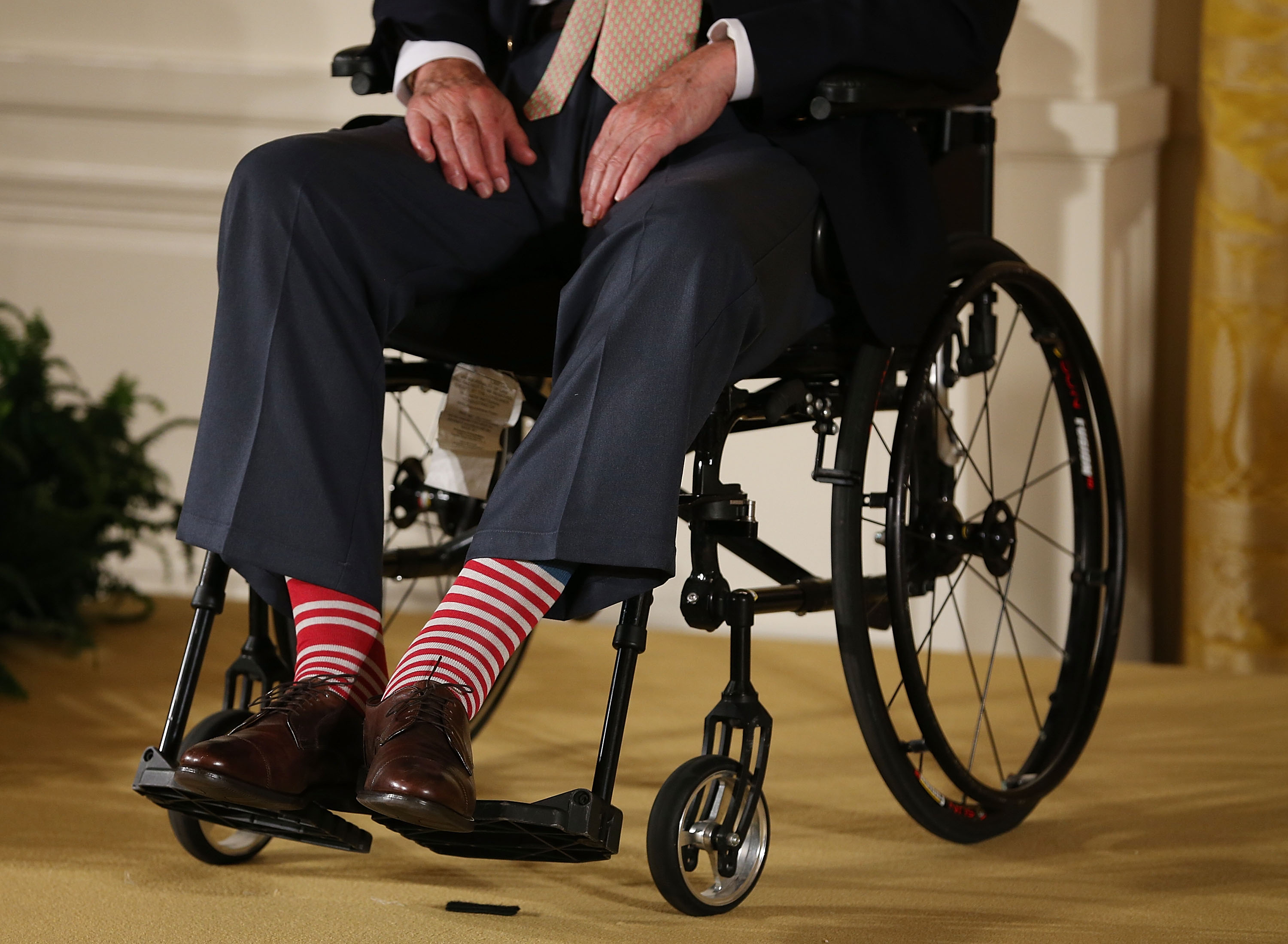 Former President George H. W. Bush wears red stripped socks as he sits in a wheelchair during an event in the East Room at the White House, July 15, 2013 in Washington, DC. Bush joined President Obama in hosting the event to honor the 5,000th Daily Point of Light Award winner.  (Photo by Mark Wilson/Getty Images)