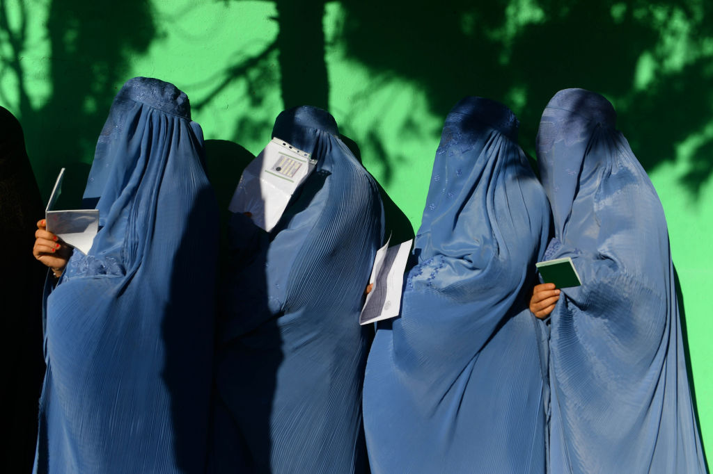 Afghan women wait in line to vote at a polling centre for the country's legislative election in Herat province on October 20, 2018.